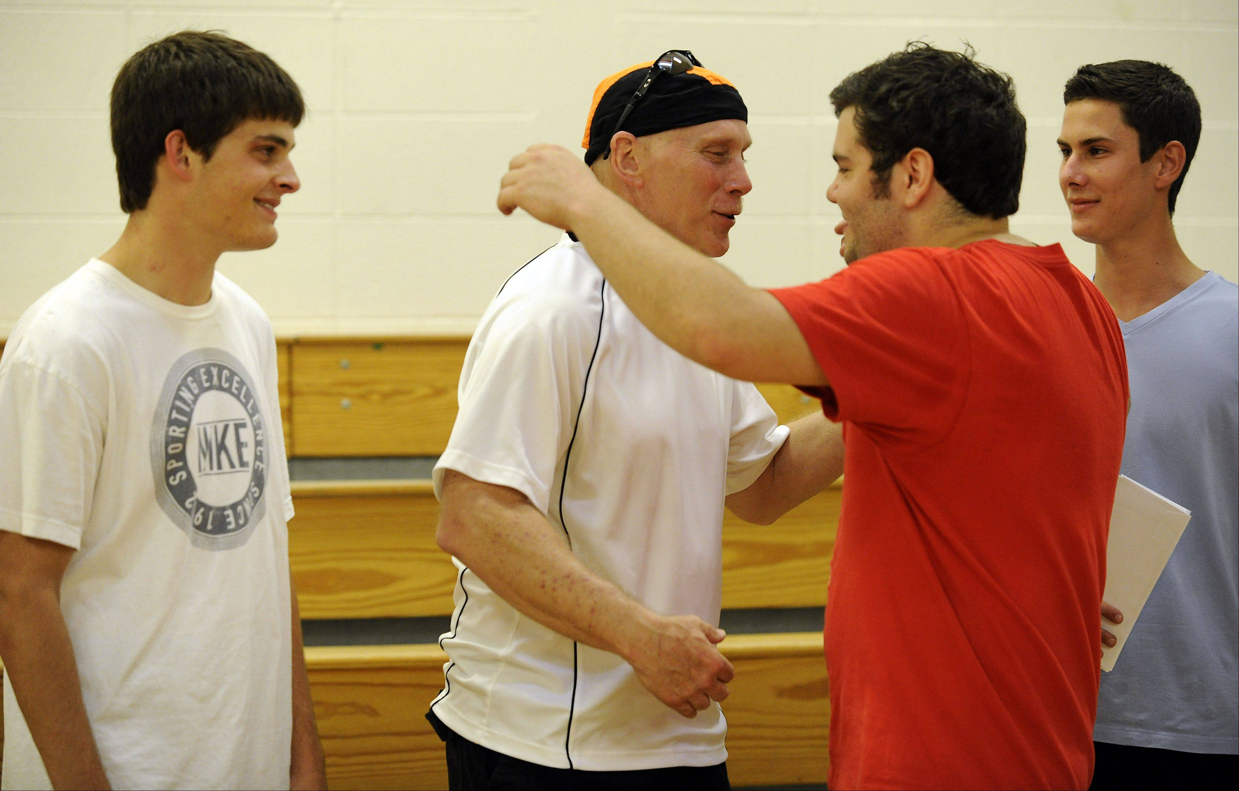 Brett O'Conner, 21, of Libertyville gives his former coach Randy Kuceyeski a big hug at the charity dodgeball game, to raise money for his throat cancer treatments. At left is Chris Jungmann, 20; at right is Sean Milbourne, 20, all former Libertyville High School graduates who organized the event.