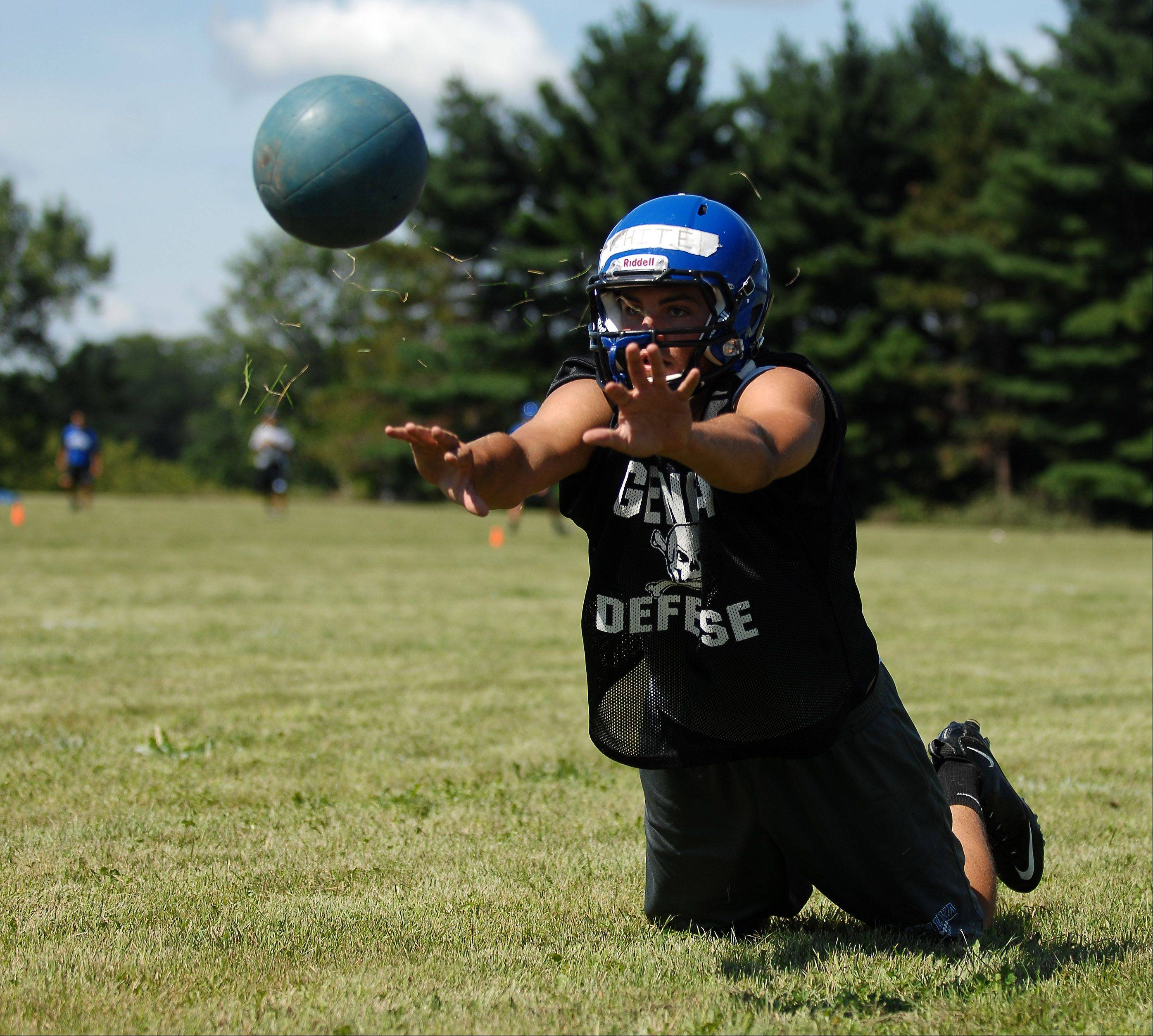 Drew White lunges and throws a medicine ball during the first day of football practice for Geneva High School at the former Broadview Academy site in La Fox Wednesday.