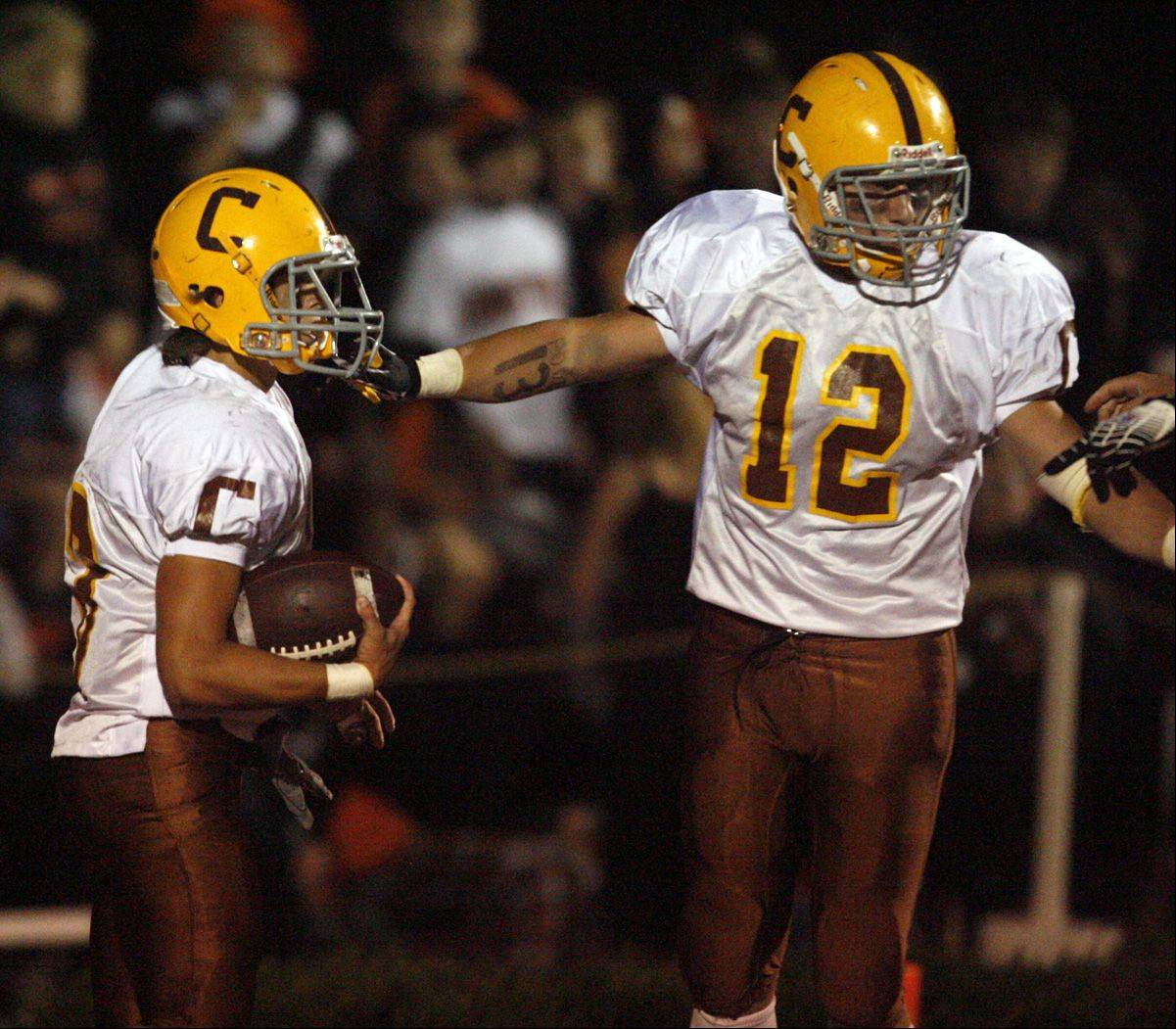 Carmel's Jordan Kos and Michael Panico celebrate after scoring a touchdown against Libertyville last season.