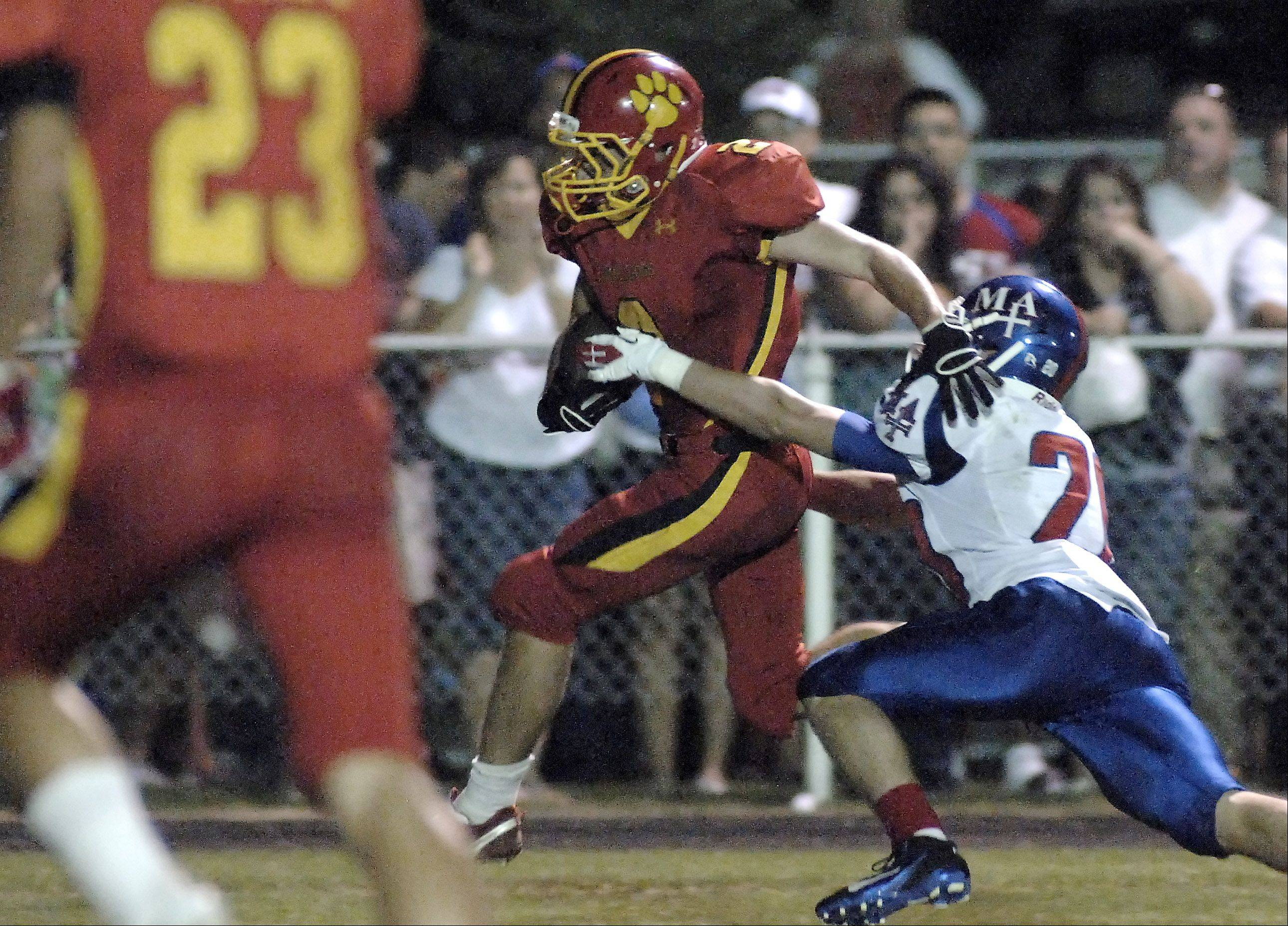 Batavia's Jon Gray shakes off Marmion Academy's Kyle Kozak on his way to a touchdown in the first quarter on Friday, August 26.