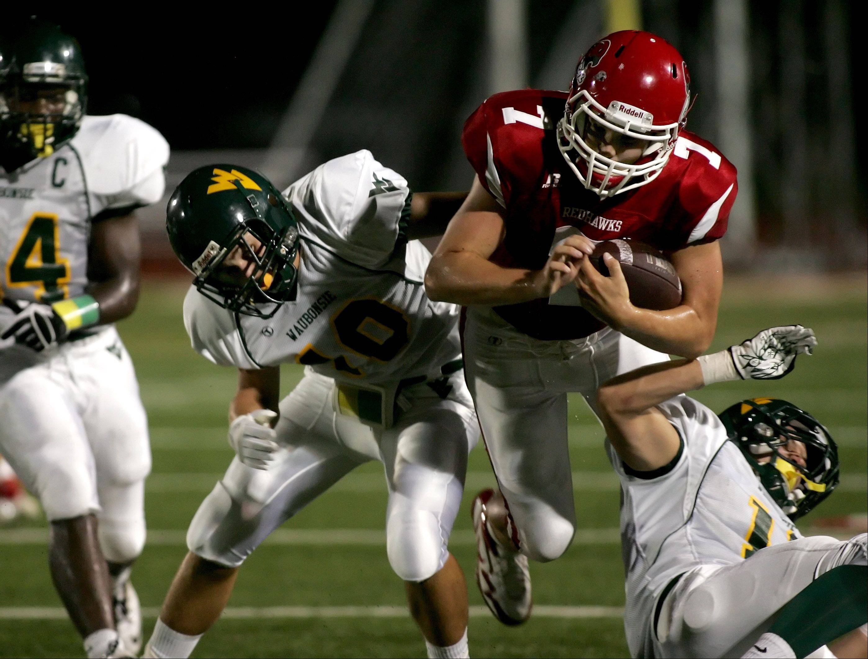 Bev Horne/bhorne@dailyherald.com Connor Mersch, left and Jim Delaney, right, of Waubonsie Valley tackle quarterback Ian Lewandowski of Naperville Central in football action Friday in Naperville.