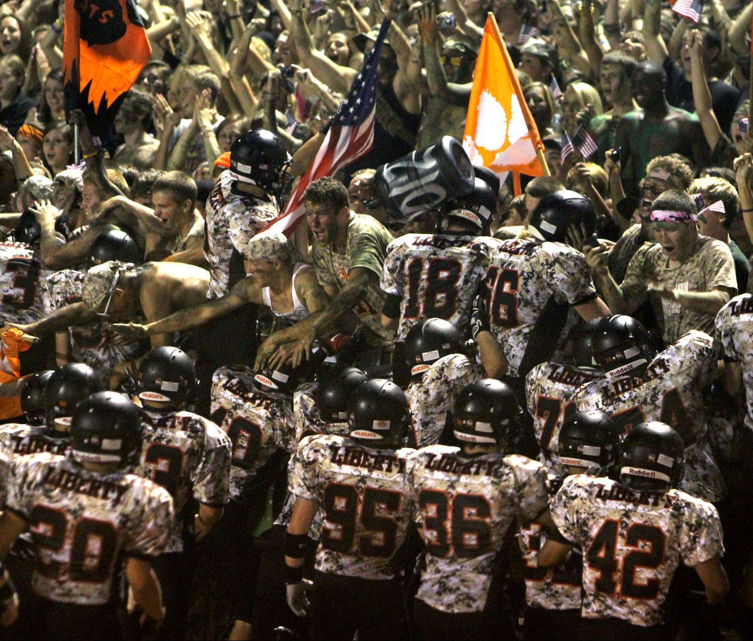Libertyville players, wearing special camouflage uniforms, leap into the stands after taking the field on military appreciation night.