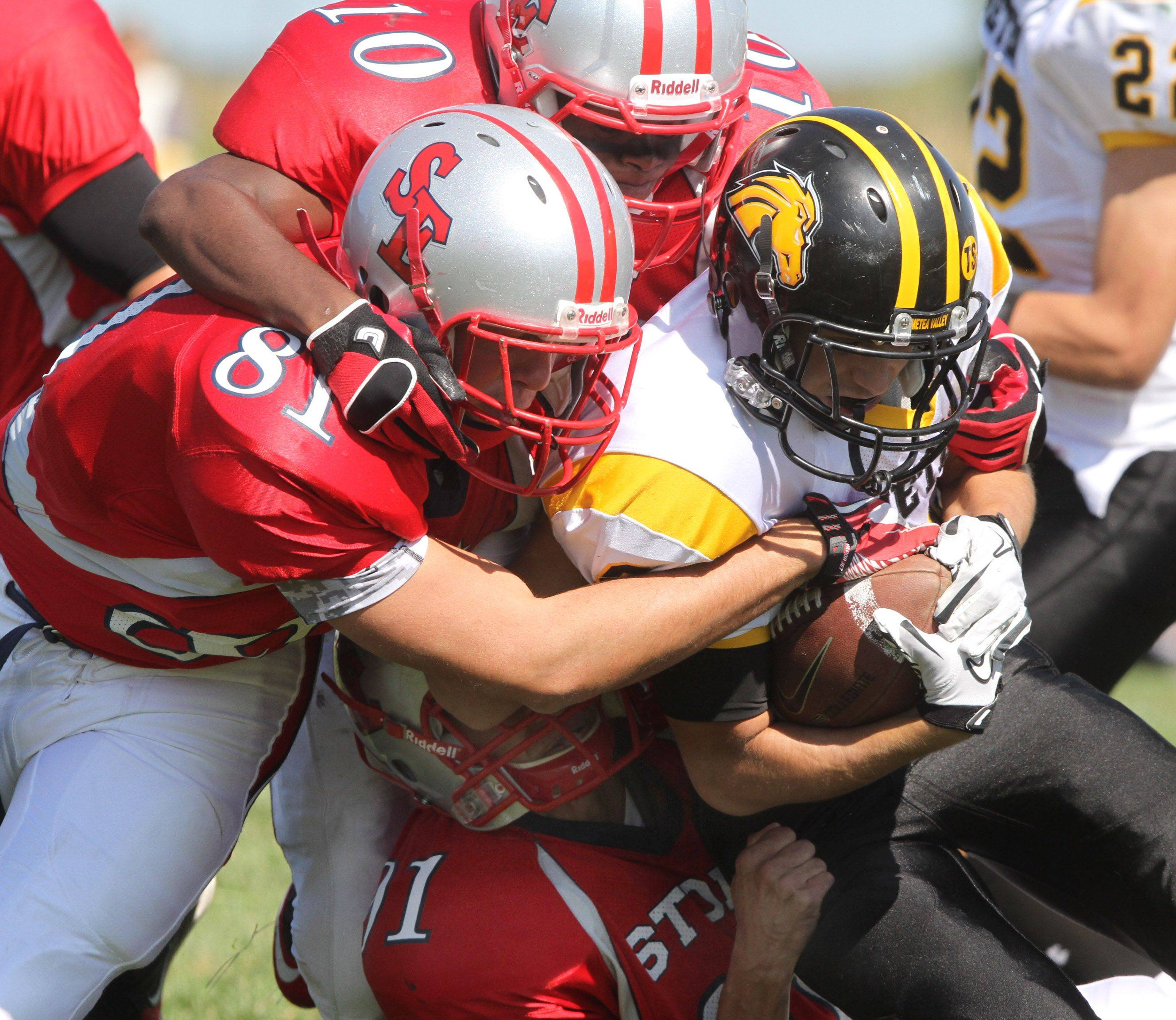 Metea Valley's Alex Hagemaster is dragged down by South Elgin defenders at South Elgin on Saturday, September 17th.