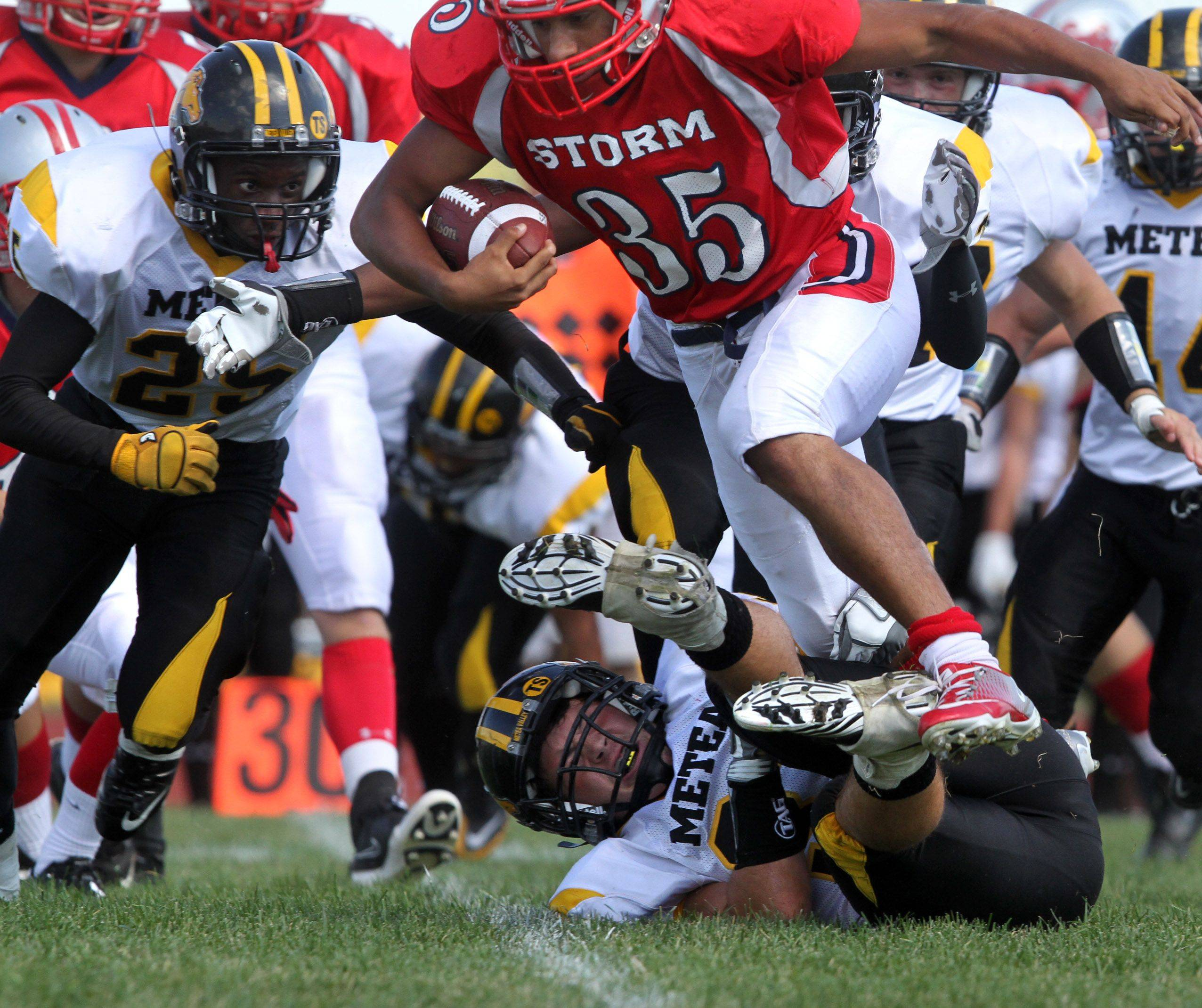 South Elgin's Adolfo Pacheco runs over a Metea Valley defender scoring a touchdown at South Elgin on Saturday, September 17th.