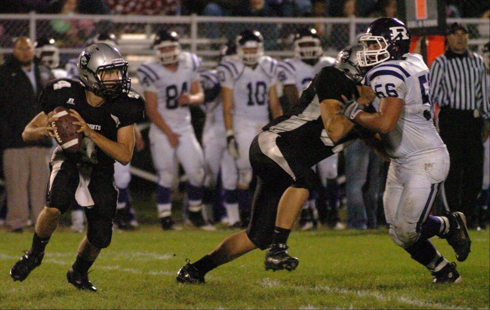 Kaneland quarterback Drew David attempts to escape Rochelle defenders Friday at Kaneland High School.