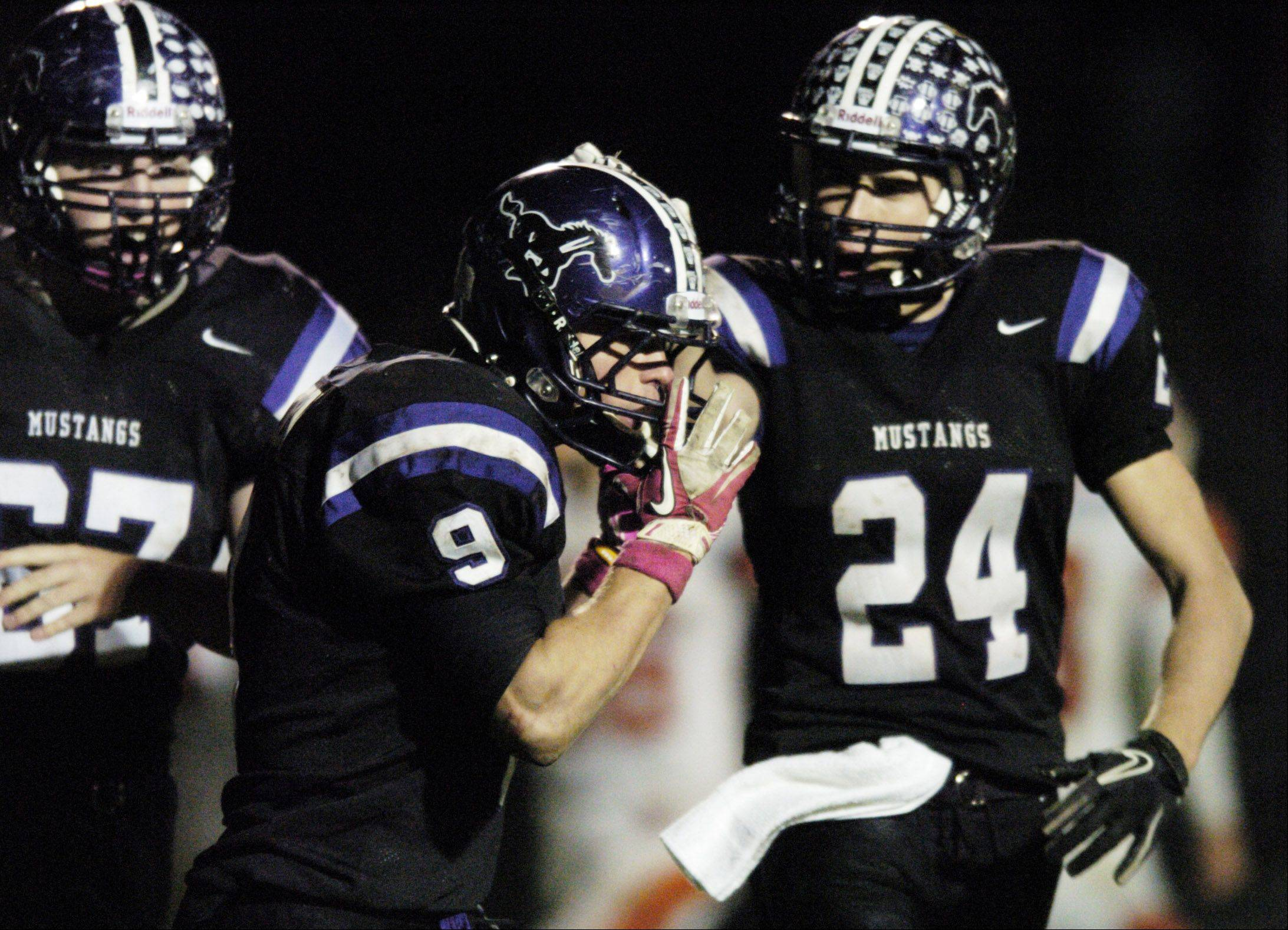 Week 9- Rolling Meadows' Garrett Peterson, middle, is congratulated by teammate Ryan Gunderson for his second touchdown of the game against Hersey.