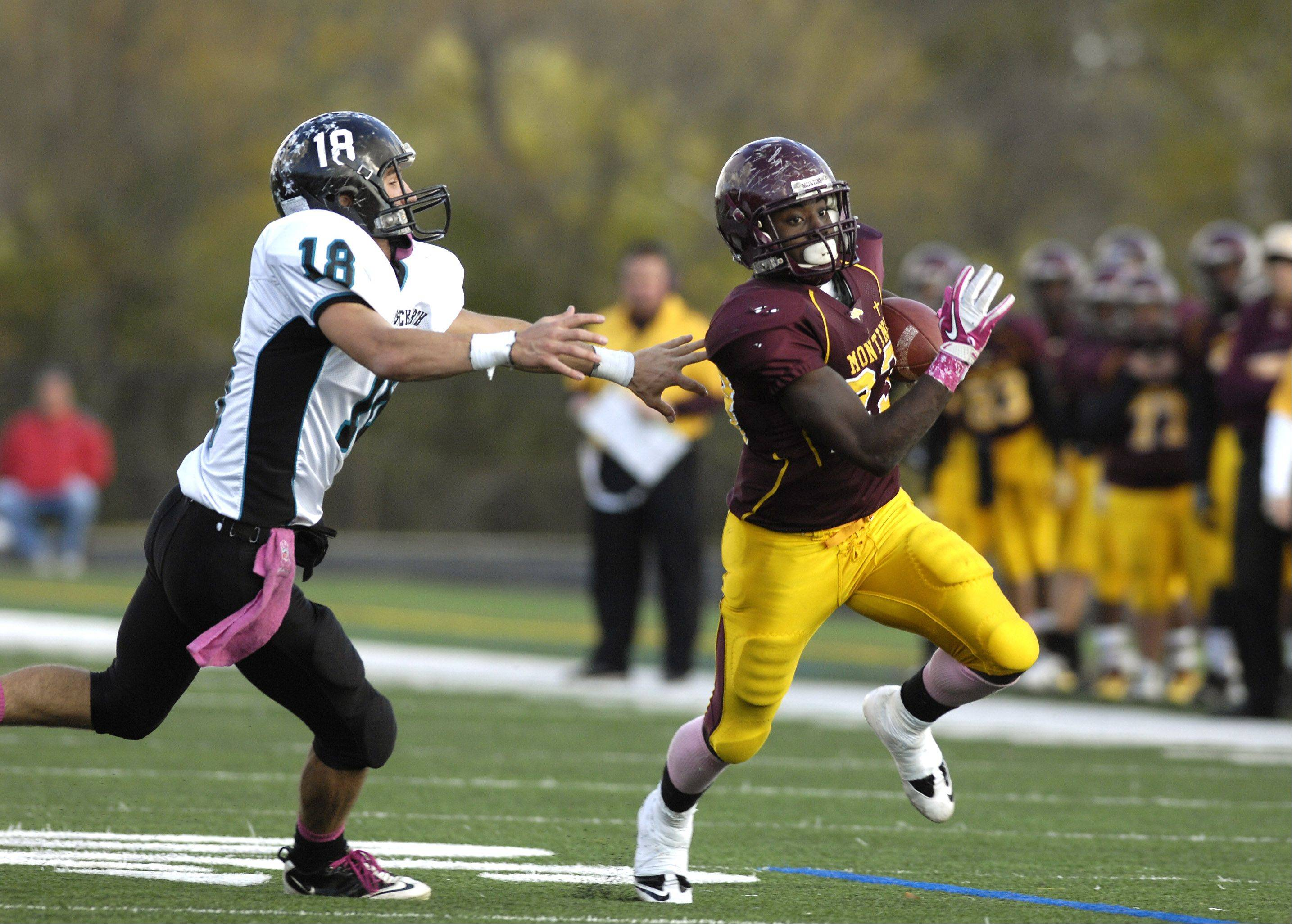 Dimitri Taylor of Montini High School scrambles away from Brian Loftin of Woodstock North, to score a 4th quarter touchdown, during the IHSA 5A playoff game.