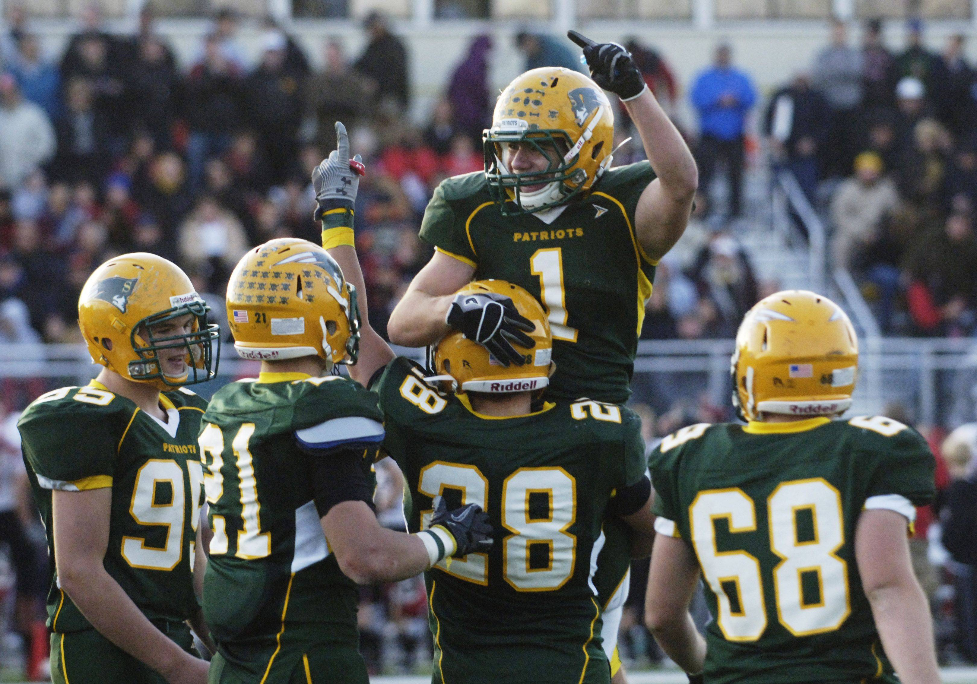 JOE LEWNARD/jlewnard@dailyherald.com Stevenson's Kevin Foley, top, celebrates with teammates after the Patriots defeated Maine South during Saturday's 8A playoff game.