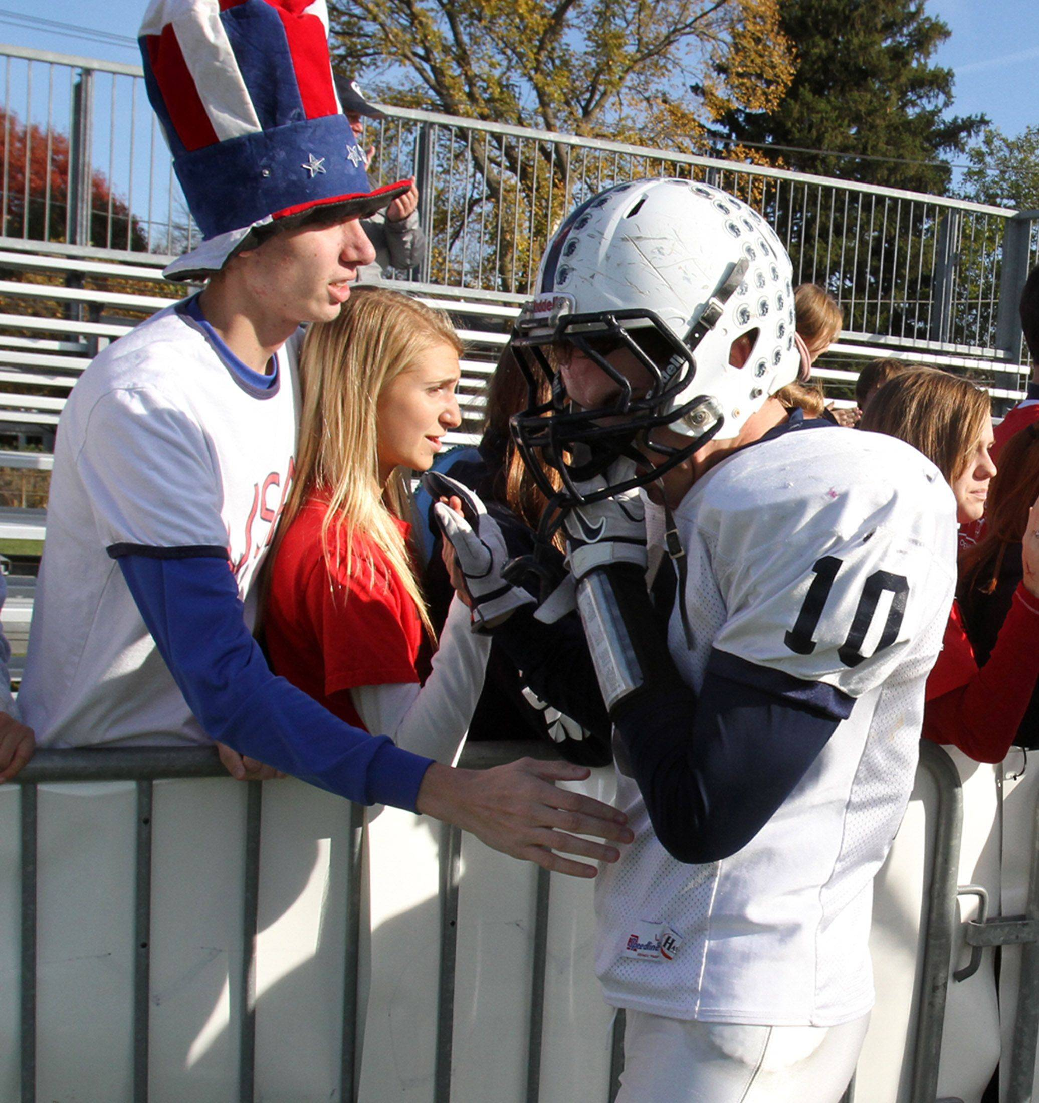 Cary-Grove linebacker Patrick Snell gets a hand from Trojans' fans after C-G's loss to Nazareth Academy on Saturday.