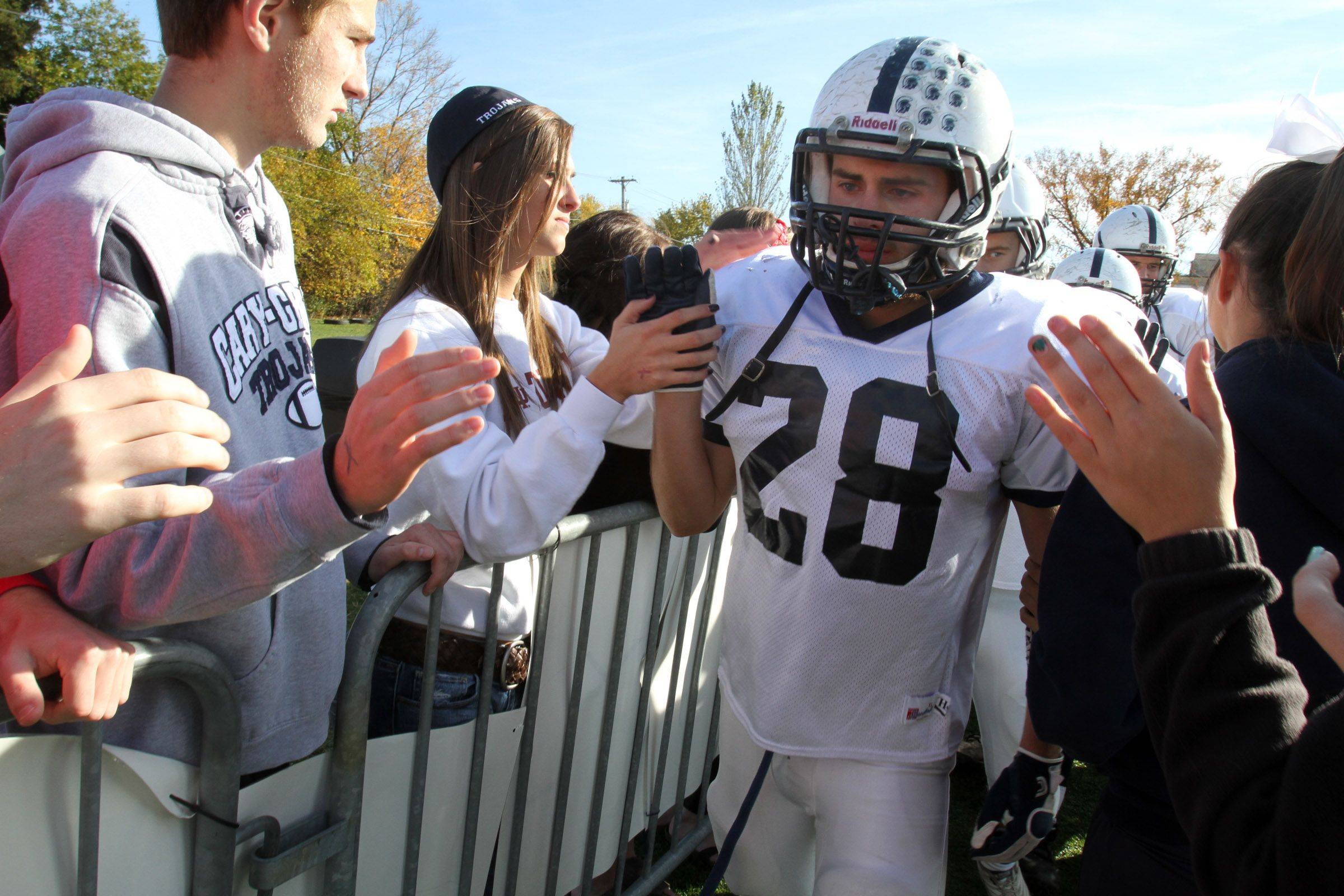 Cary-Grove running-back Connor Carlson gets a hand from fans after gthe Trojans' loss to Nazareth Academy on Saturday, November 5th.