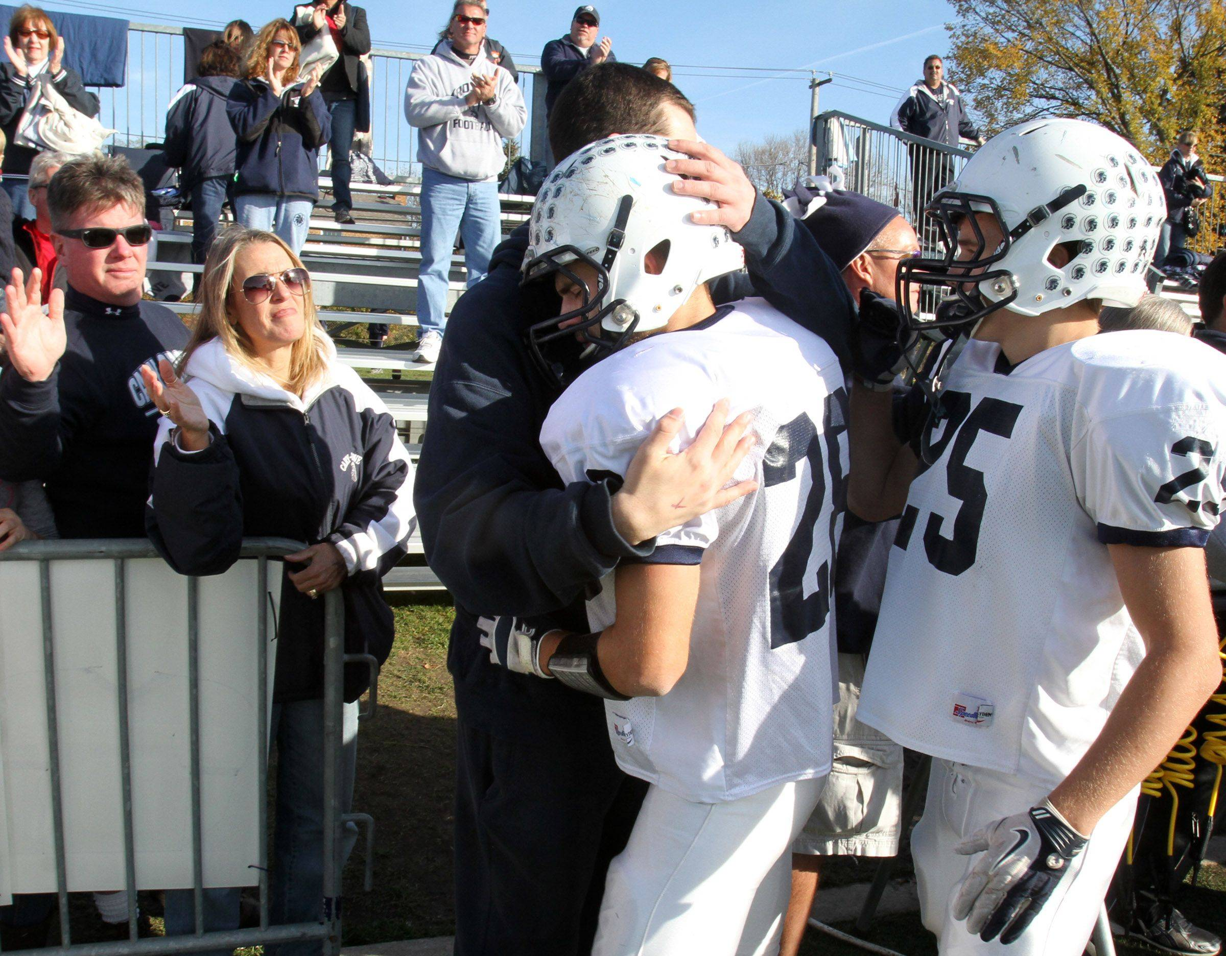 Cary-Grove running-back Connor Carlson gets consoled by a Trojans' coach as fans await after C-G's loss to Nazareth Academy on Saturday, November 5th.