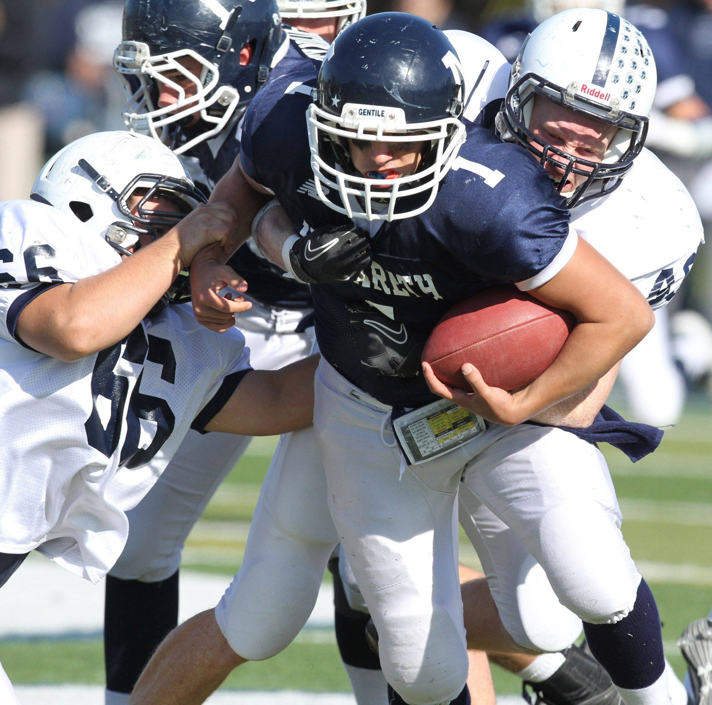 Cary-Grove lineman Andrew Snyder, left, and linebacker Brock Bussenger drag down Nazareth Academy quarterback Samuel Poulos on Saturday, November 5th.