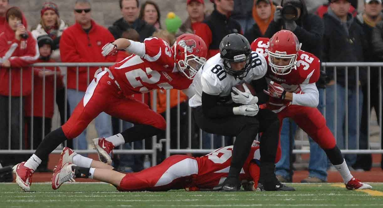 Paul Michna/pmichna@dailyherald.comPat Clark,left, and Ross Murphy of Naperille Central bring down Chandler Piekarski of Bolingbrook at Naperville Central football Class 8A semifinals Saturday.