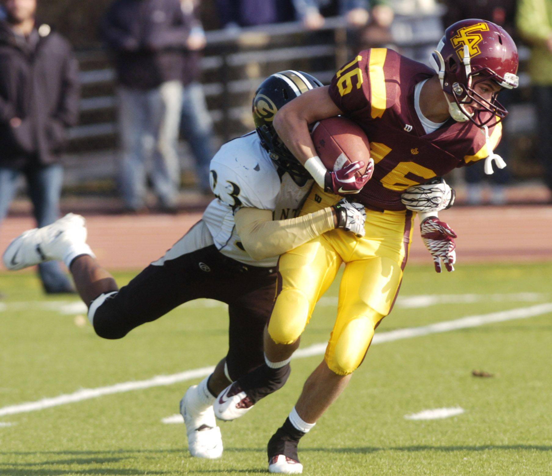 Richie Wehman III of Loyola Academy is tackled by Tremel Smith of Glenbard North.