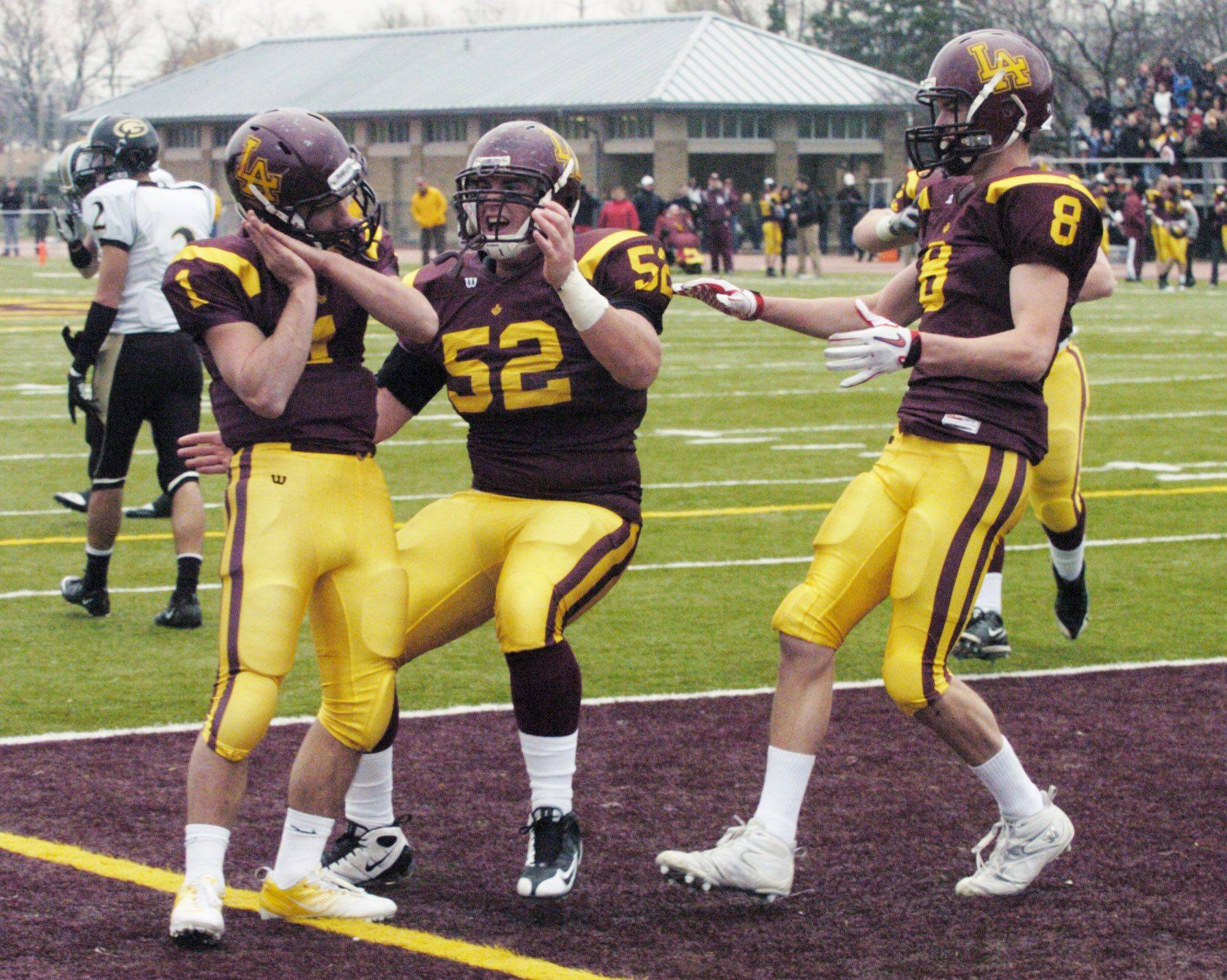 Loyola Academy's William Pavilos, left, celebrates his touchdown with teammate Robert Delaney, middle, and Charlie Dowdle during Saturday's win against Glenbard North.
