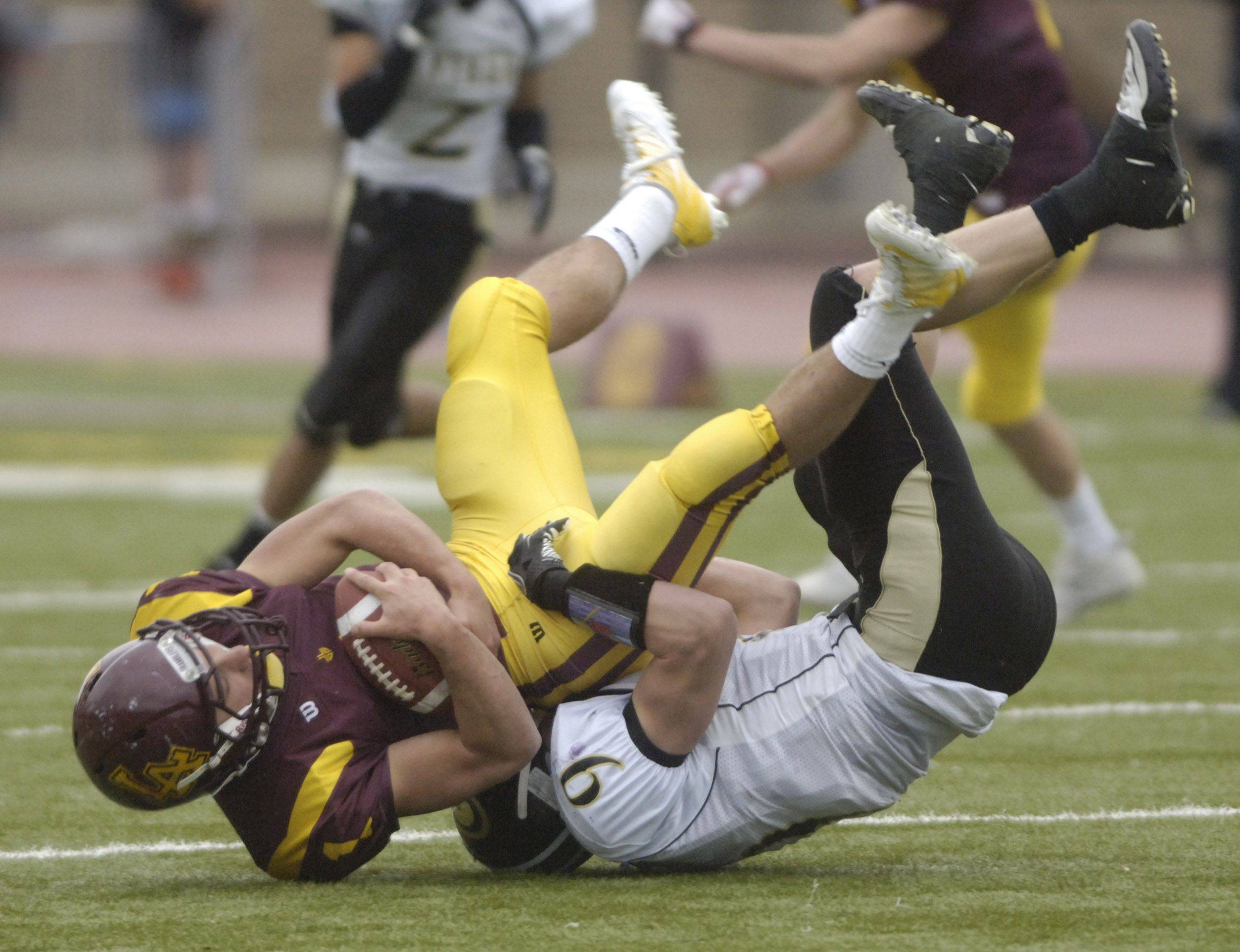 William Pavilos of Loyola Academy gets upended on a tackle by Hunter Week of Glenbard North.