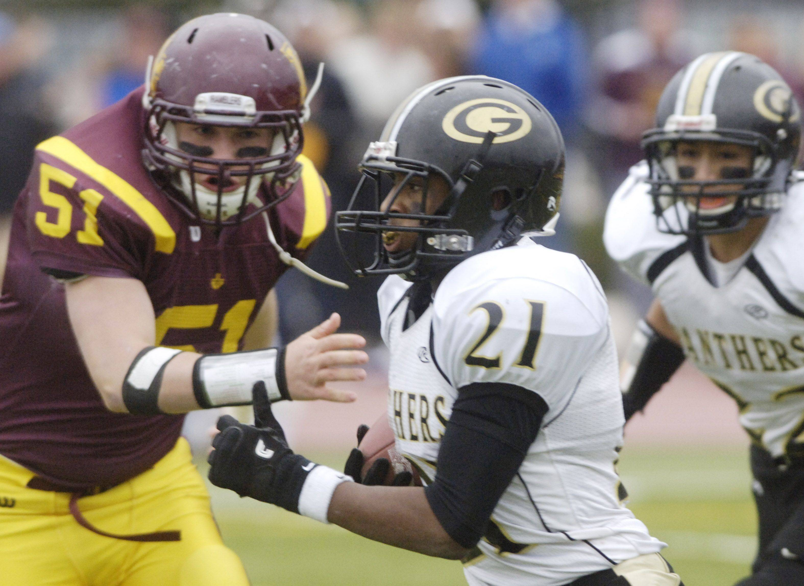 Glenbard North's Justin Jackson carries the ball as Loyola Academy's Jake Miller closes in.
