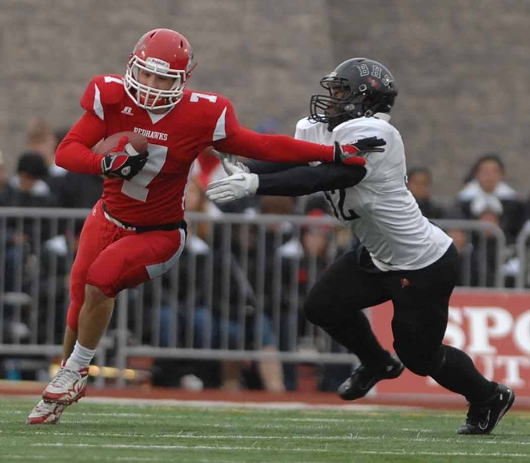 Ian Lewandowski of Naperville Central is chased by Isaac Jensen of Bolingbrook at the Naperville Central football Class 8A semifinals Saturday.