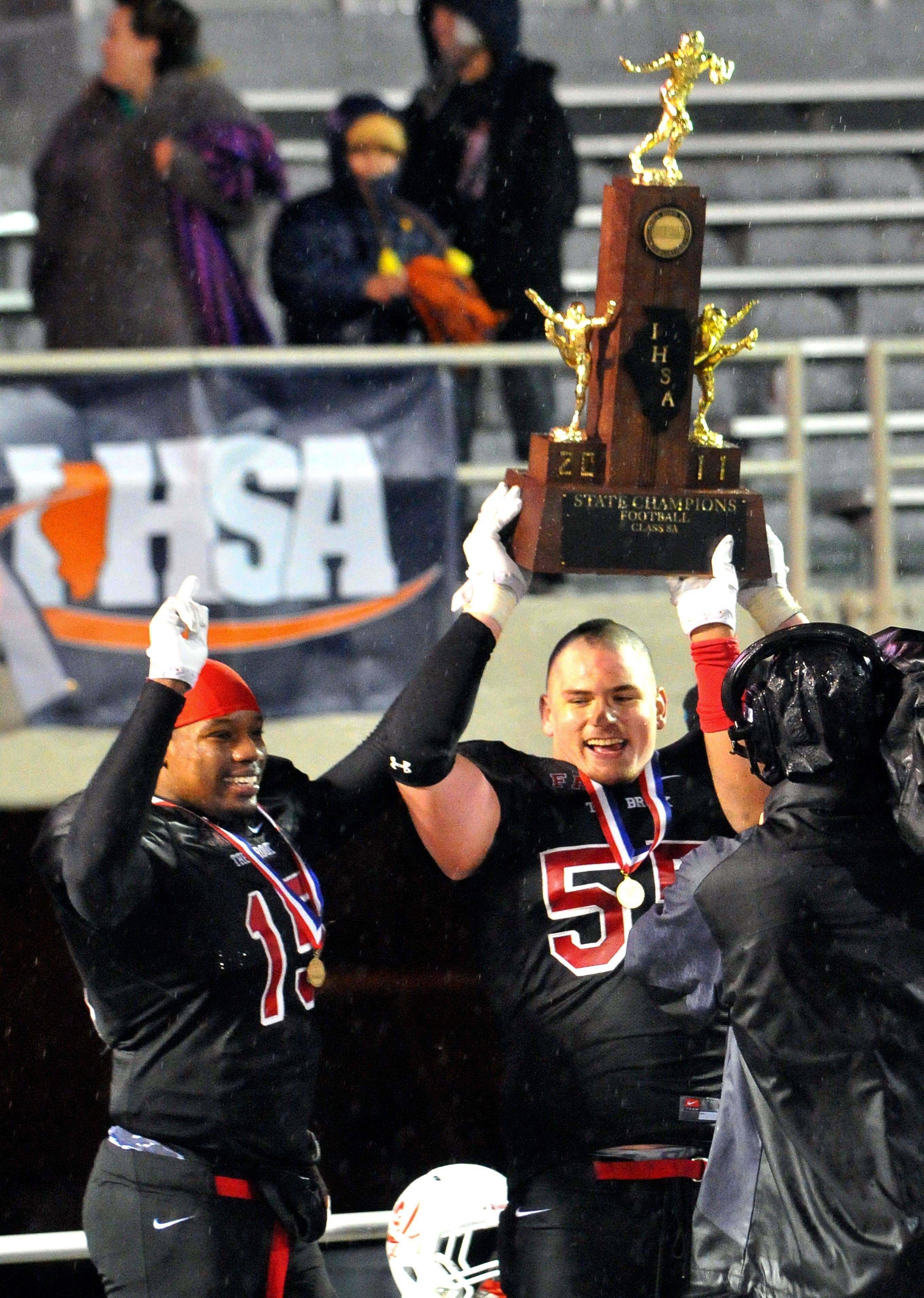 Bolingbrook's Aaron Bailey (15) and Robert Bain (55) accept the championship trophy after beating Loyola Academy 21-17 in the Class 8A state championship football game Saturday in Champaign.