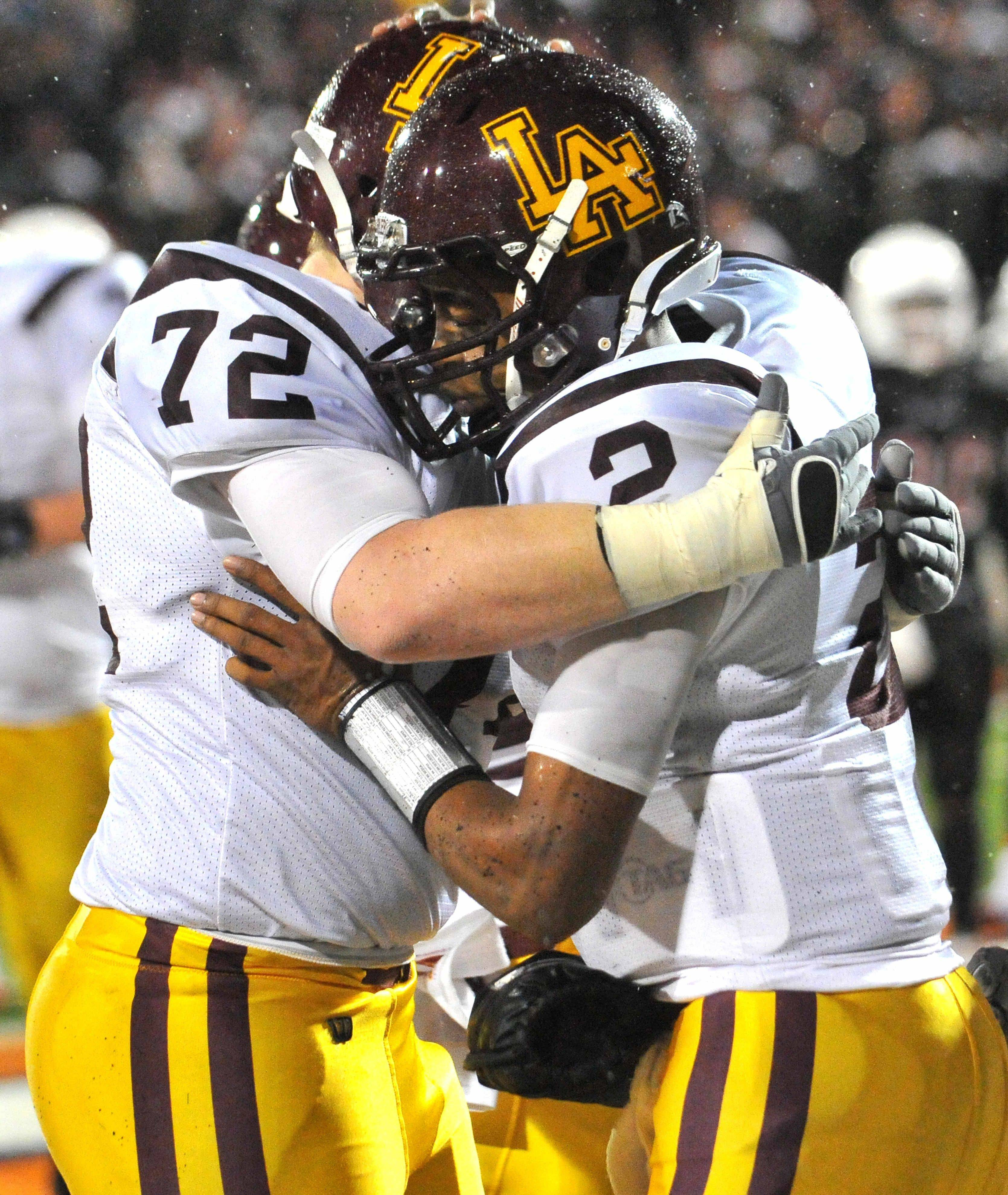 Loyola Academy Philip Spagnolo (72) hugs teammate Malcom Weaver (2) after Weaver's touchdown against Bolingbrook.