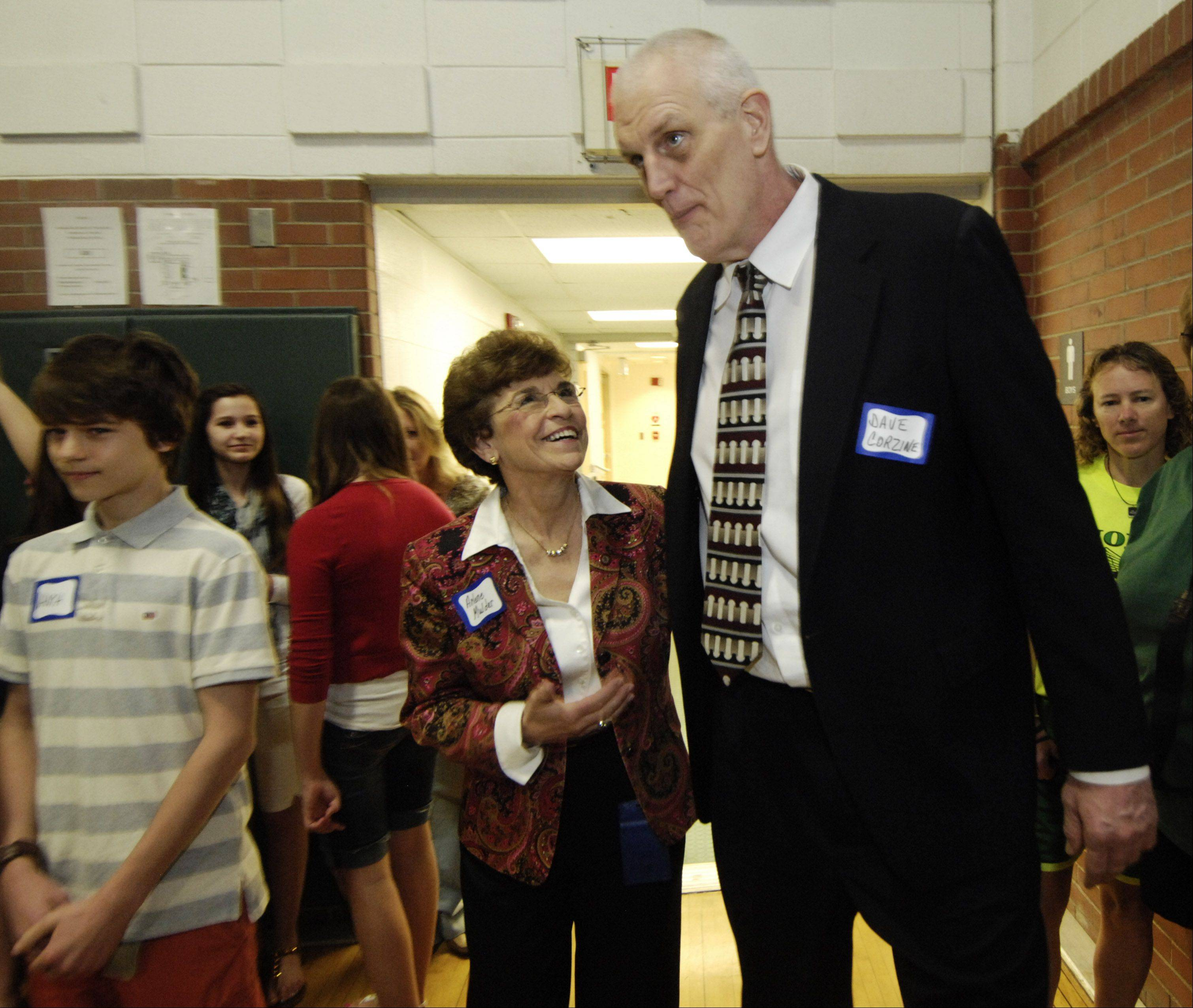 Dave Corzine, who achieved success in in high school, college and professional basketball, towers over Mayor Arlene Mulder as they enter an assembly at Thomas Middle School in Arlington Heights Thursday.