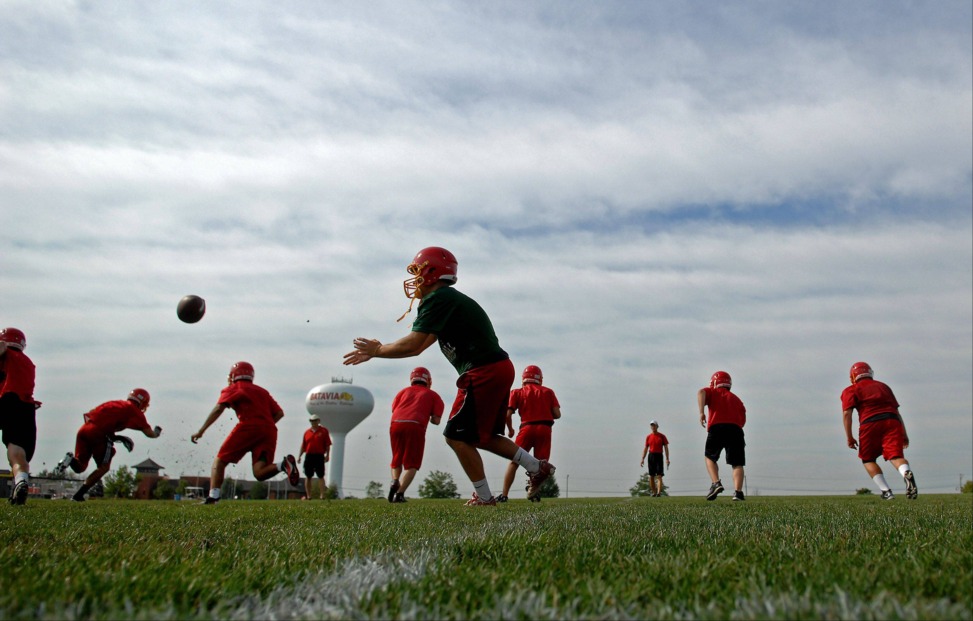 Quarterback Daniel Albrecht pitches out wide during Batavia High School's first day of football practice Wednesday.