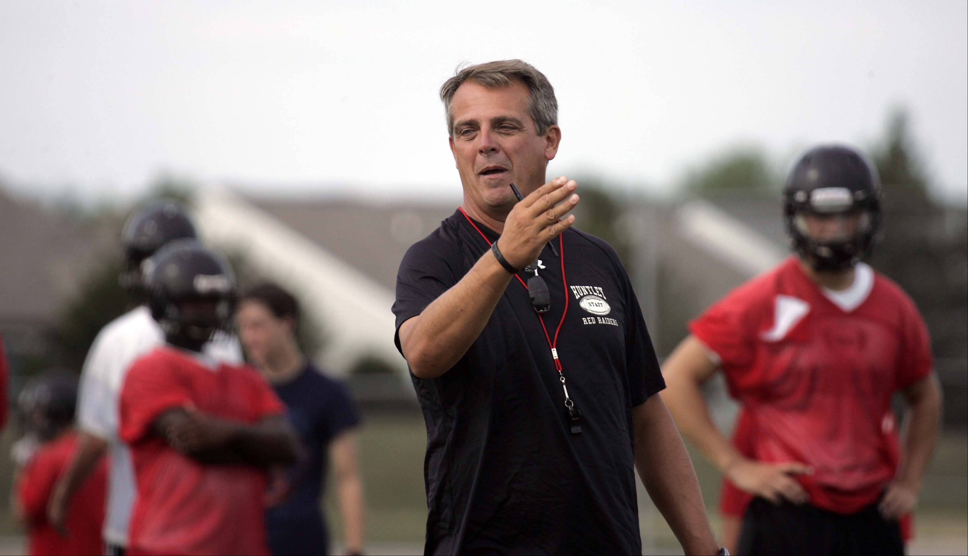 New coach John Hart works with his athletes during the first day of football practice at Huntley on Wednesday.