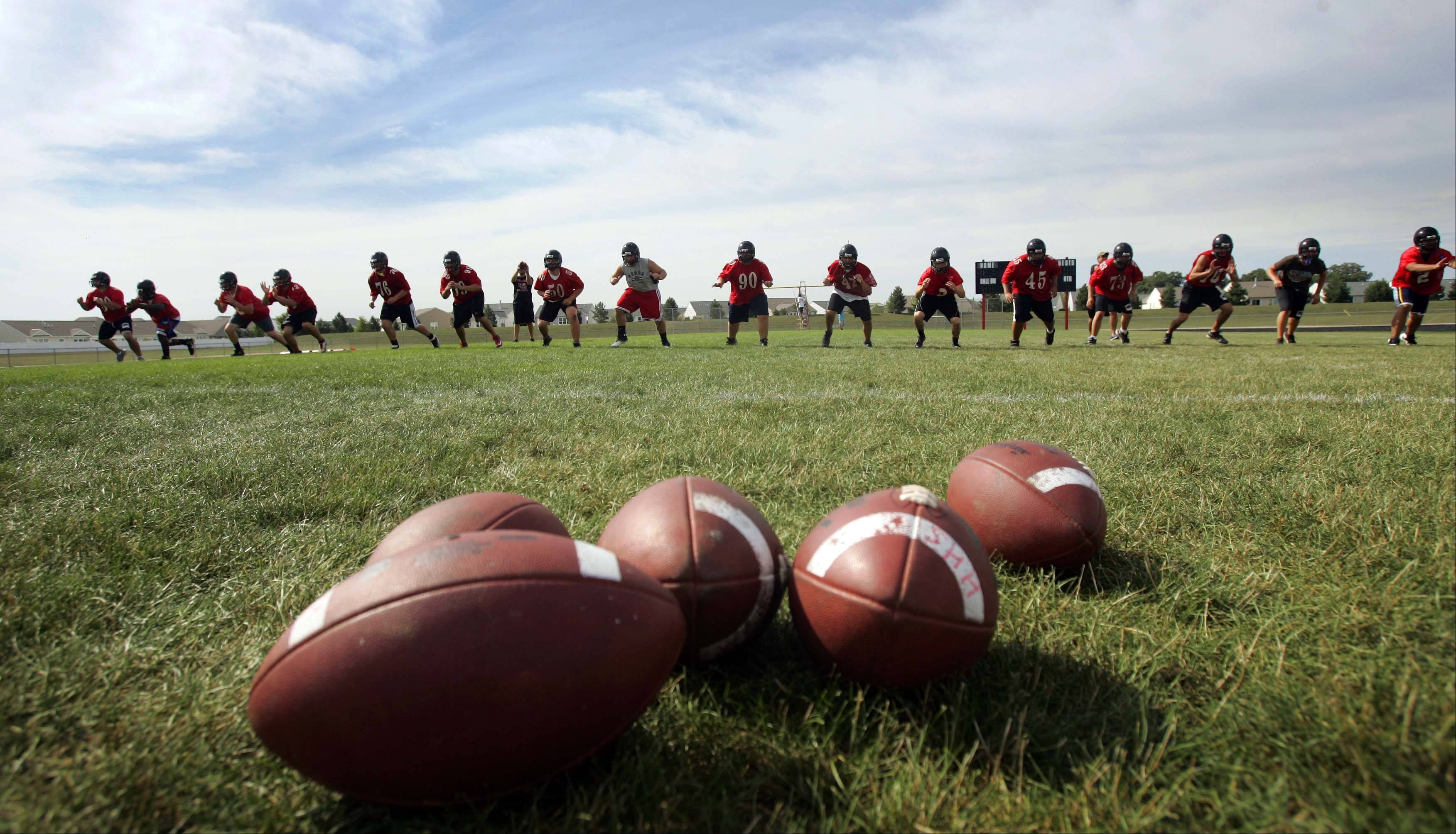 The O-line works on a drill during the first day of football practice at Huntley on Wednesday.