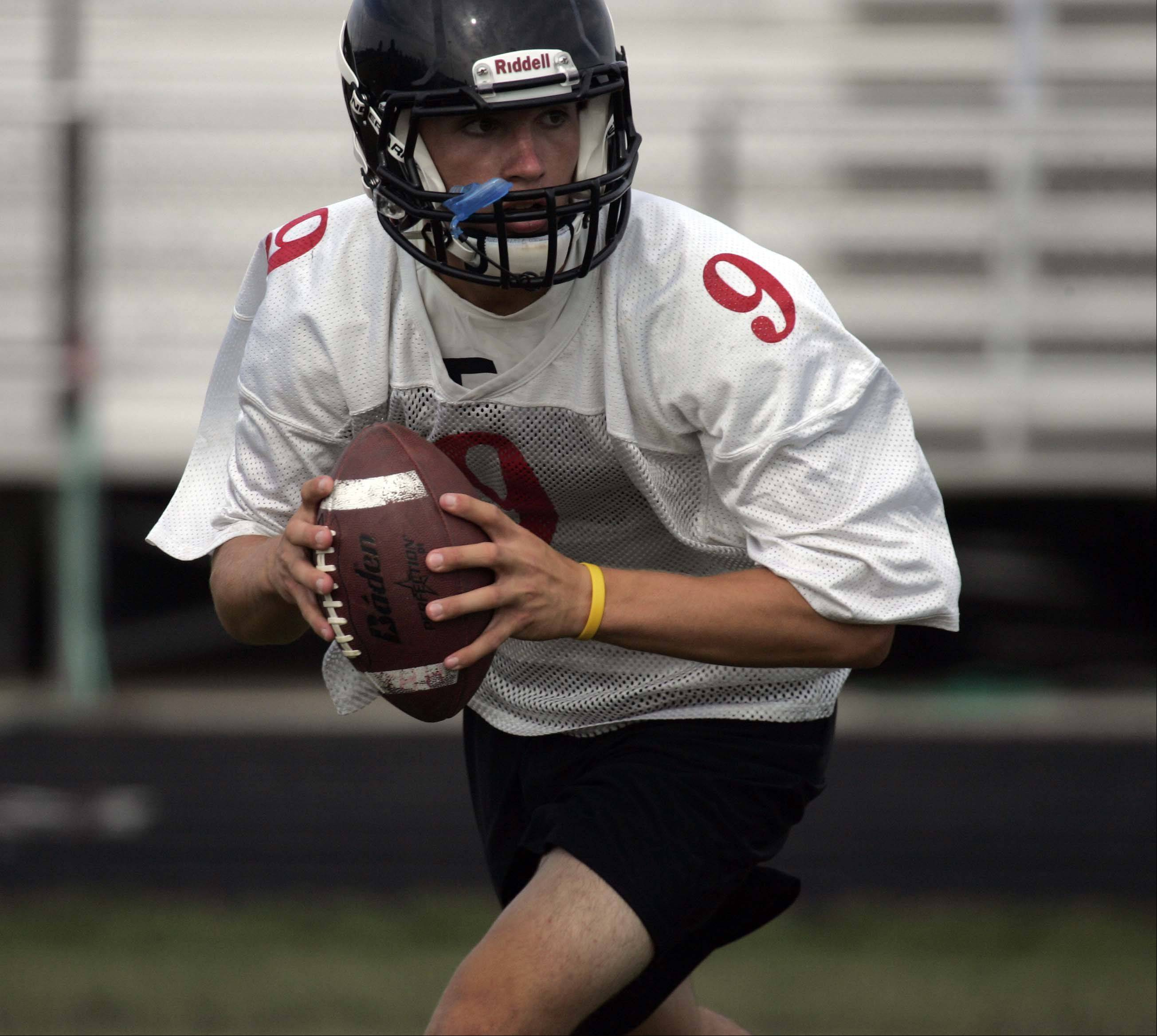 Quarterback Cameron Sallee rolls out and looks for an open reciever during the first day of football practice at Huntley on Wednesday.