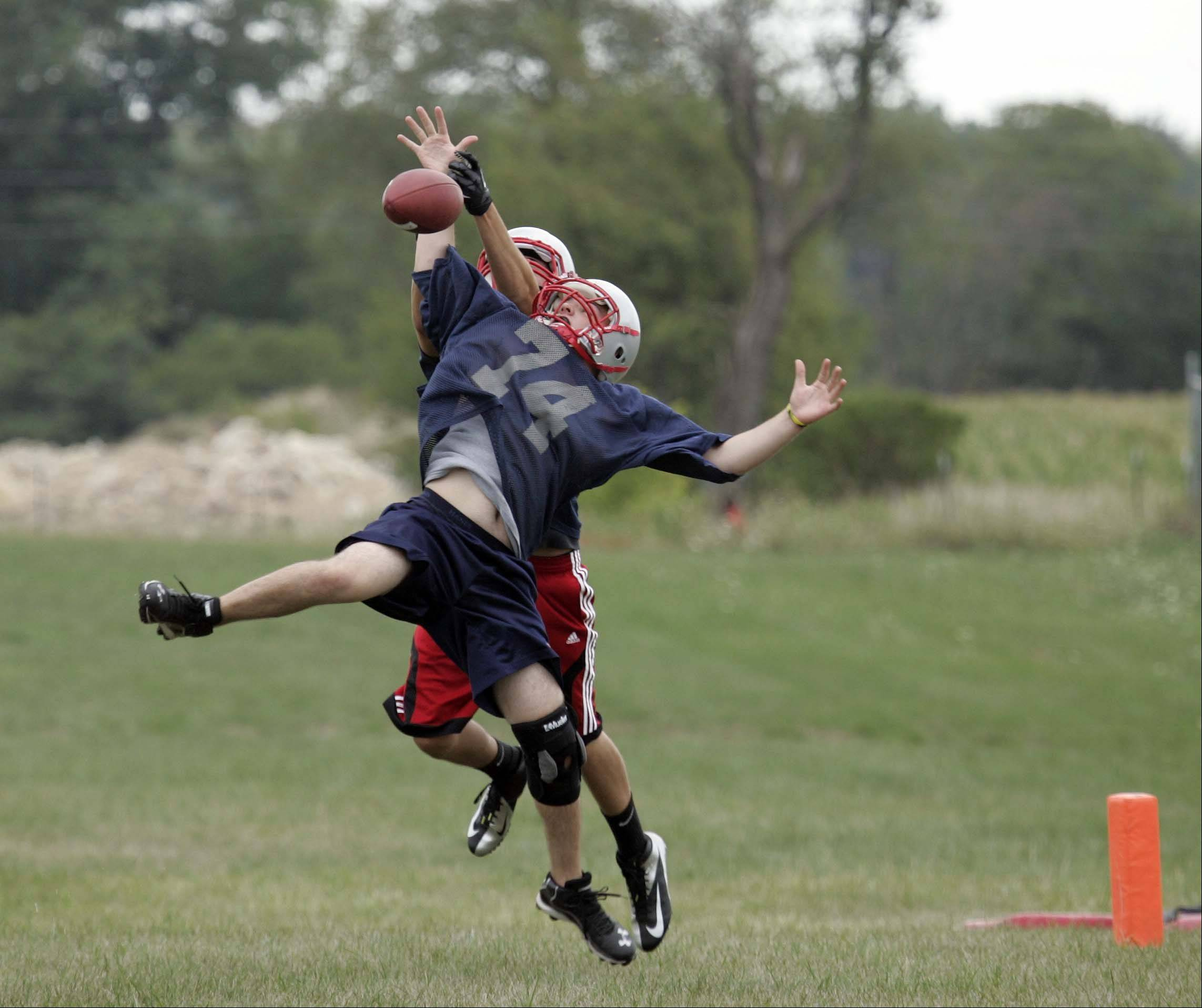 Pat McKay (74) tries to pull in a touchdown pass as Joe Lullo (82) defends during the first day of football practice at South Elgin on Wednesday.