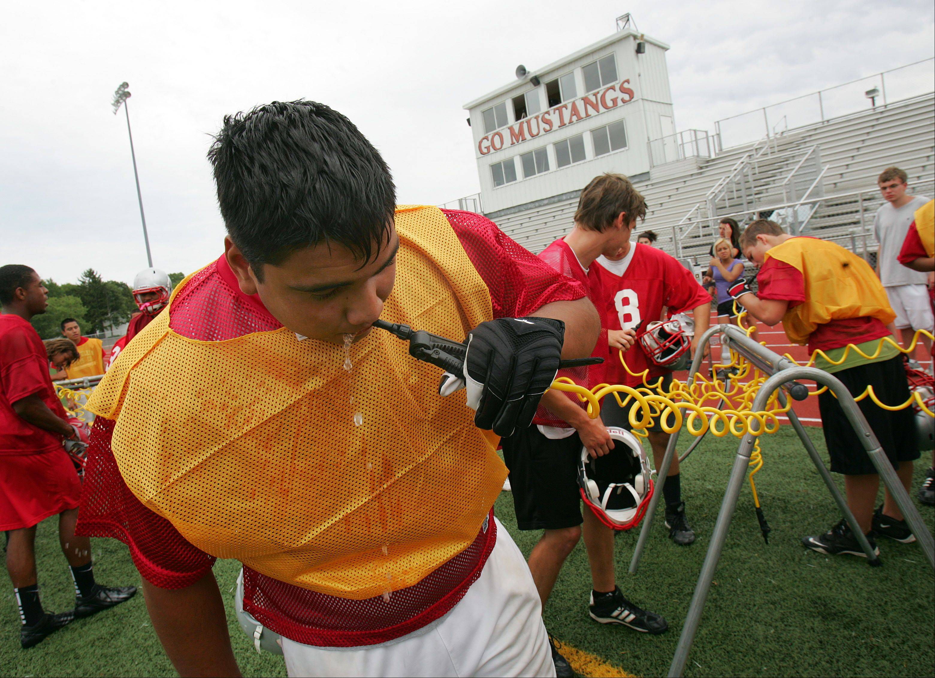 Offensive lineman Jesus Aguirre takes a hydration break during football practice Wednesday afternoon in Mundelein.