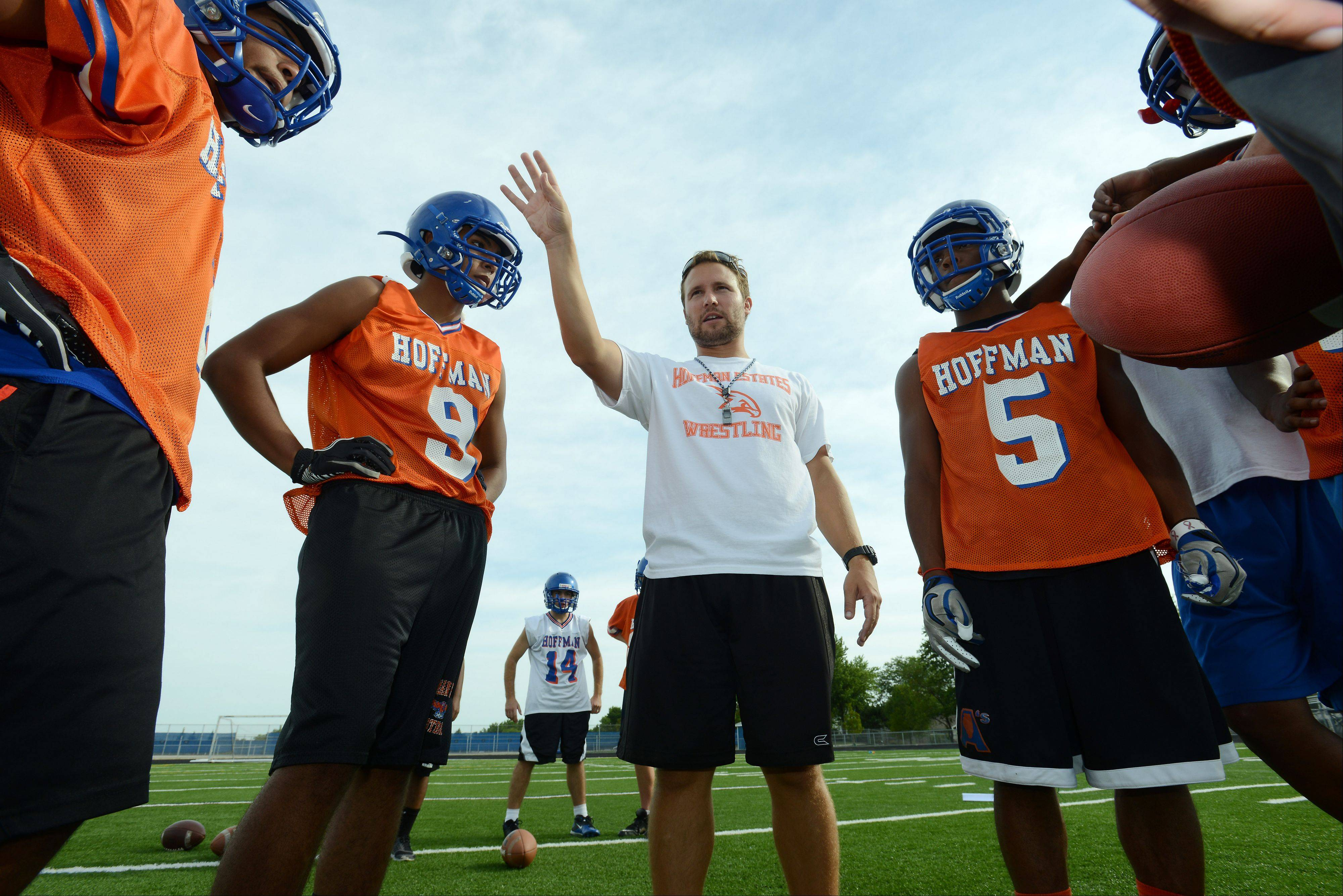 First-year Hoffman Estates football coach Eric Ilich directs his players on the first day of practice Wednesday.