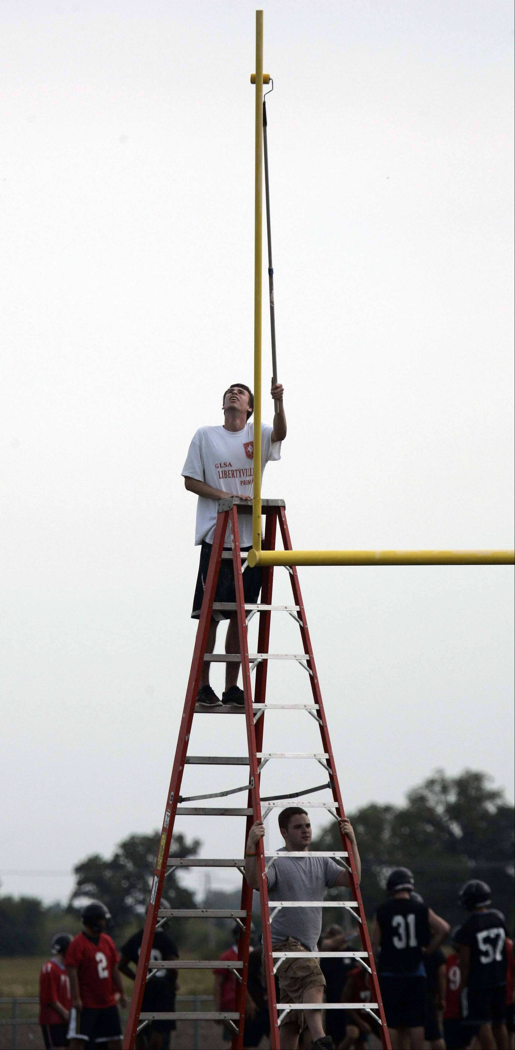 Summer painter for the school district, Kyle Lewandowski, puts a coat of yellow paint on the goal posts at Huntley High School.