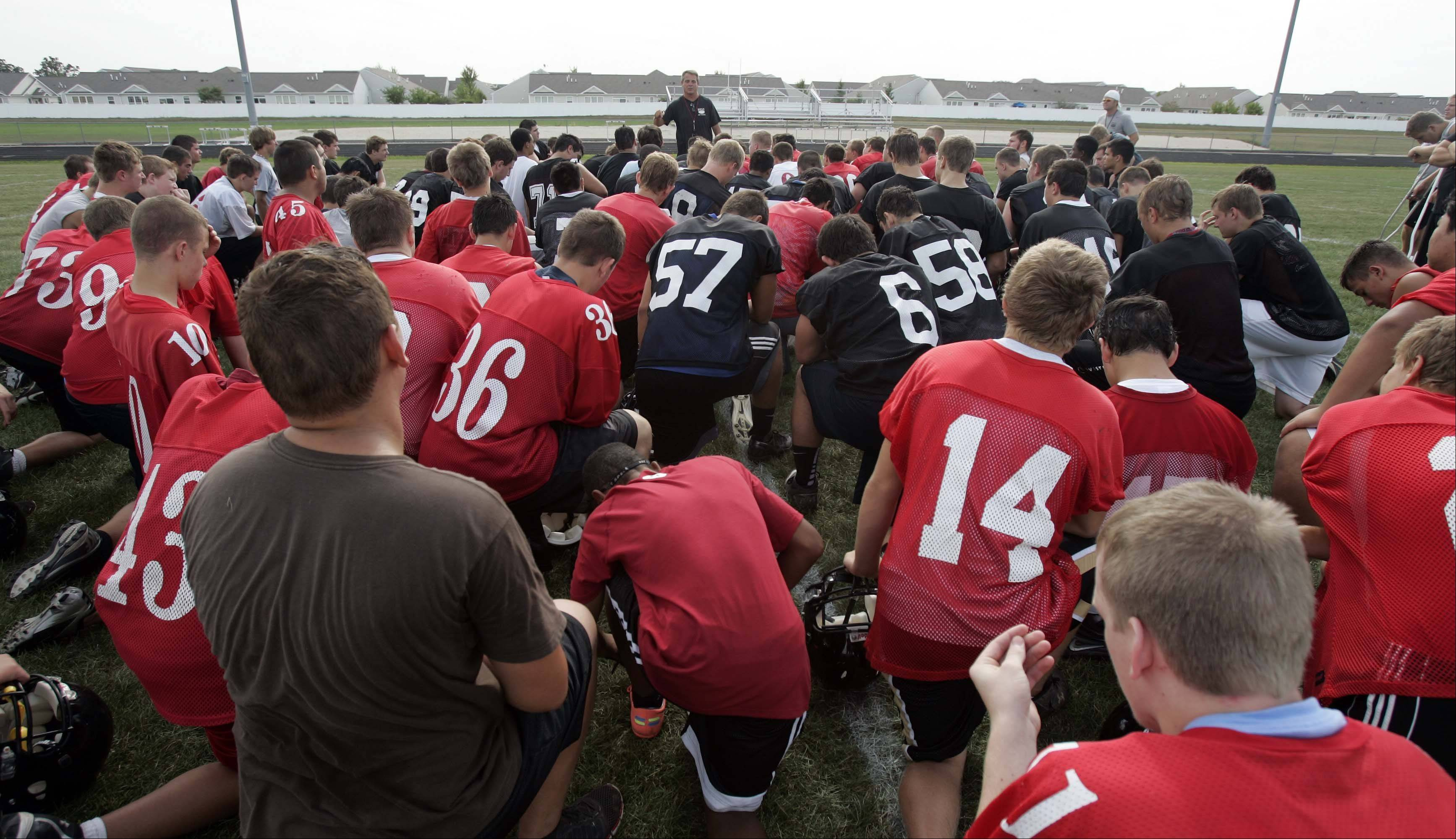 New coach John Hart talks with his athletes at Huntley High School.