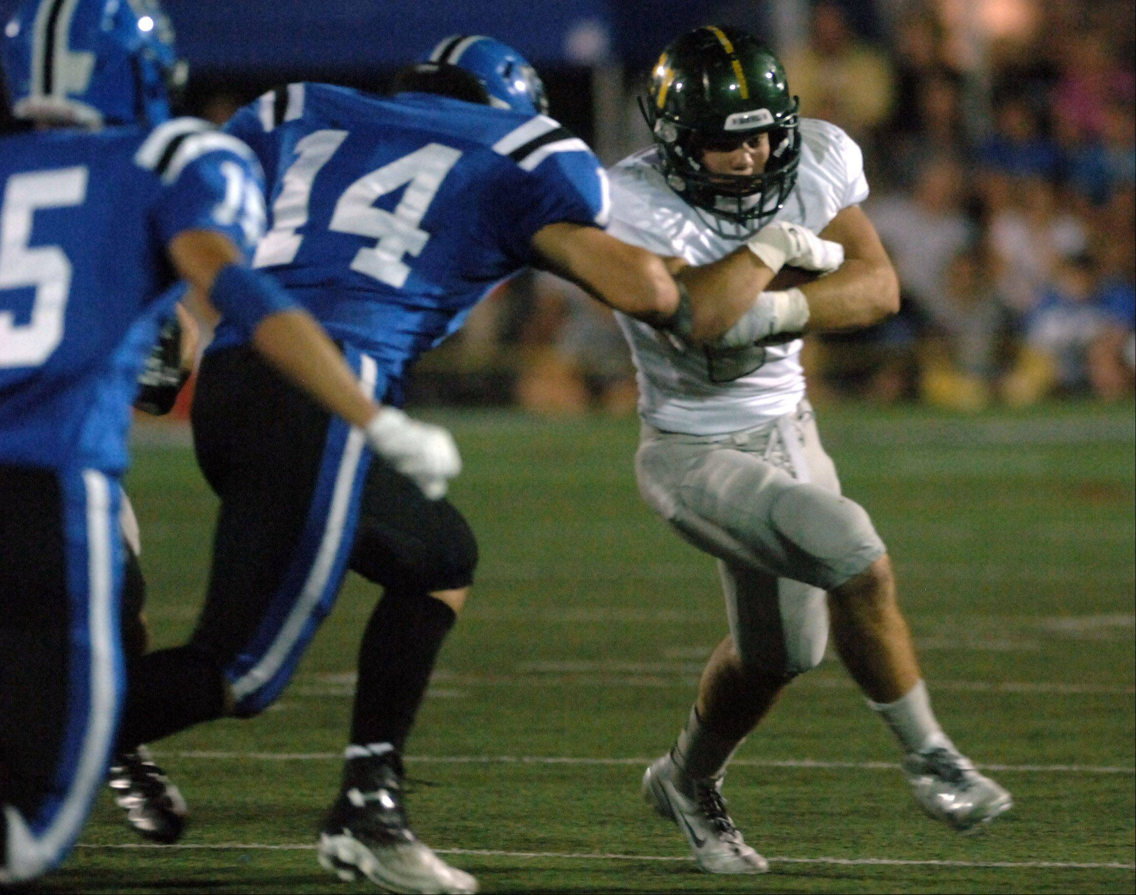 Fremd running back Jeff McGlade protects the ball from Lake Zurich's Tanner Kiser during Friday night's game in Lake Zurich.