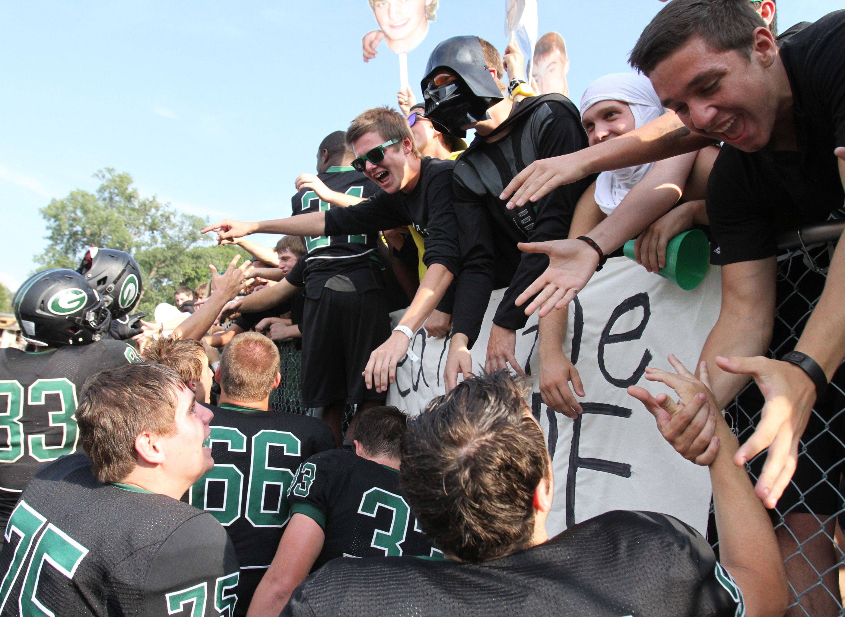 Glenbard West fans celebrate a victory with players against Wheaton Warrenville South at Glenbard West on Saturday, August 25.