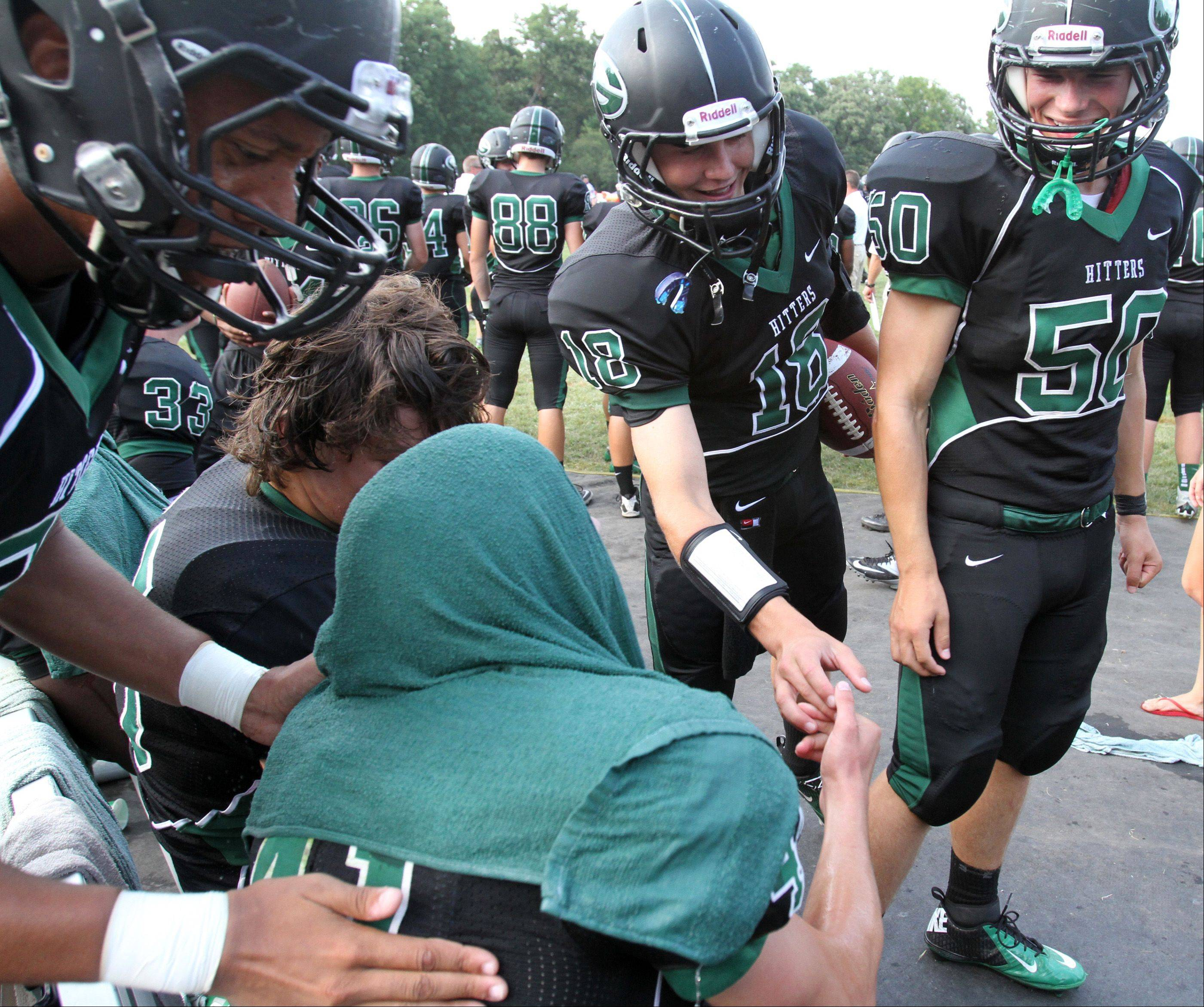 Glenbard West linebacker Eric Farley gets a cold wet-towel and hand from teammates after intercepting the ball in the third-quarter against Wheaton Warrenville South at Glenbard West on Saturday, August 25.
