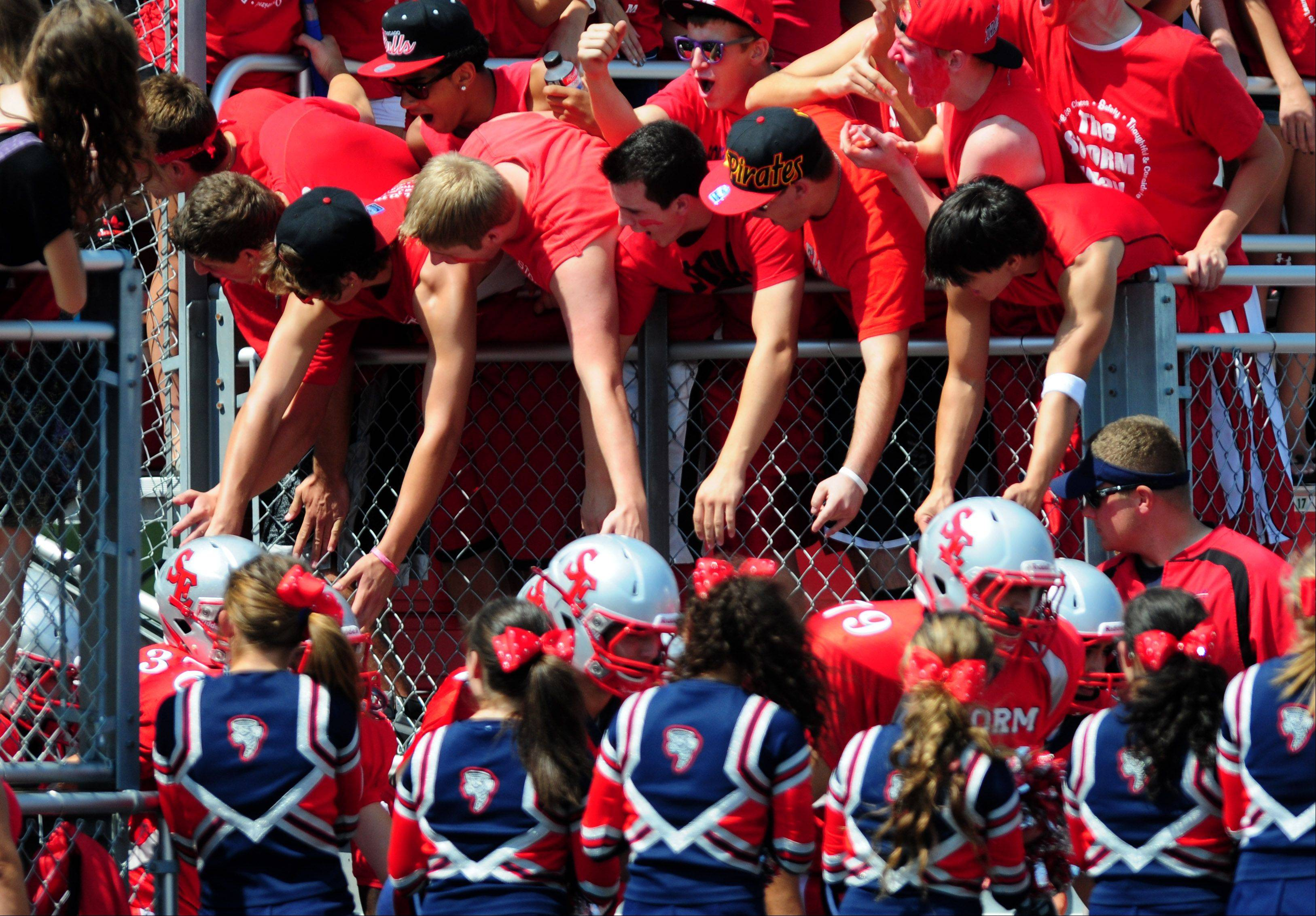 The South Elgin football team is met by low-fiving fans as they take the field Saturday to face Downers Grove South in South Elgin.