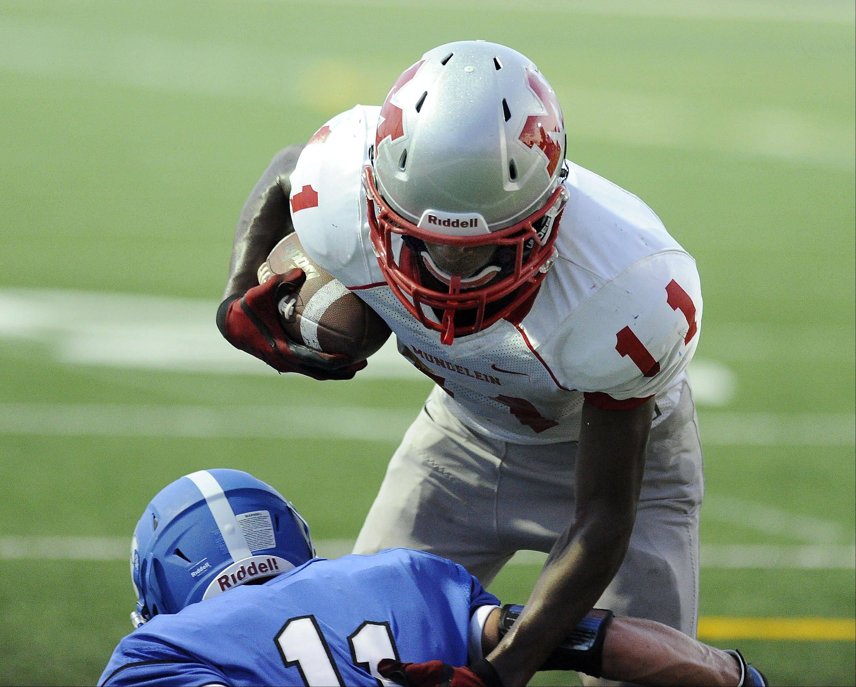 Mundelein's Chance Lindsey plows over Wheeling's Tyler Urban in the first quarter.