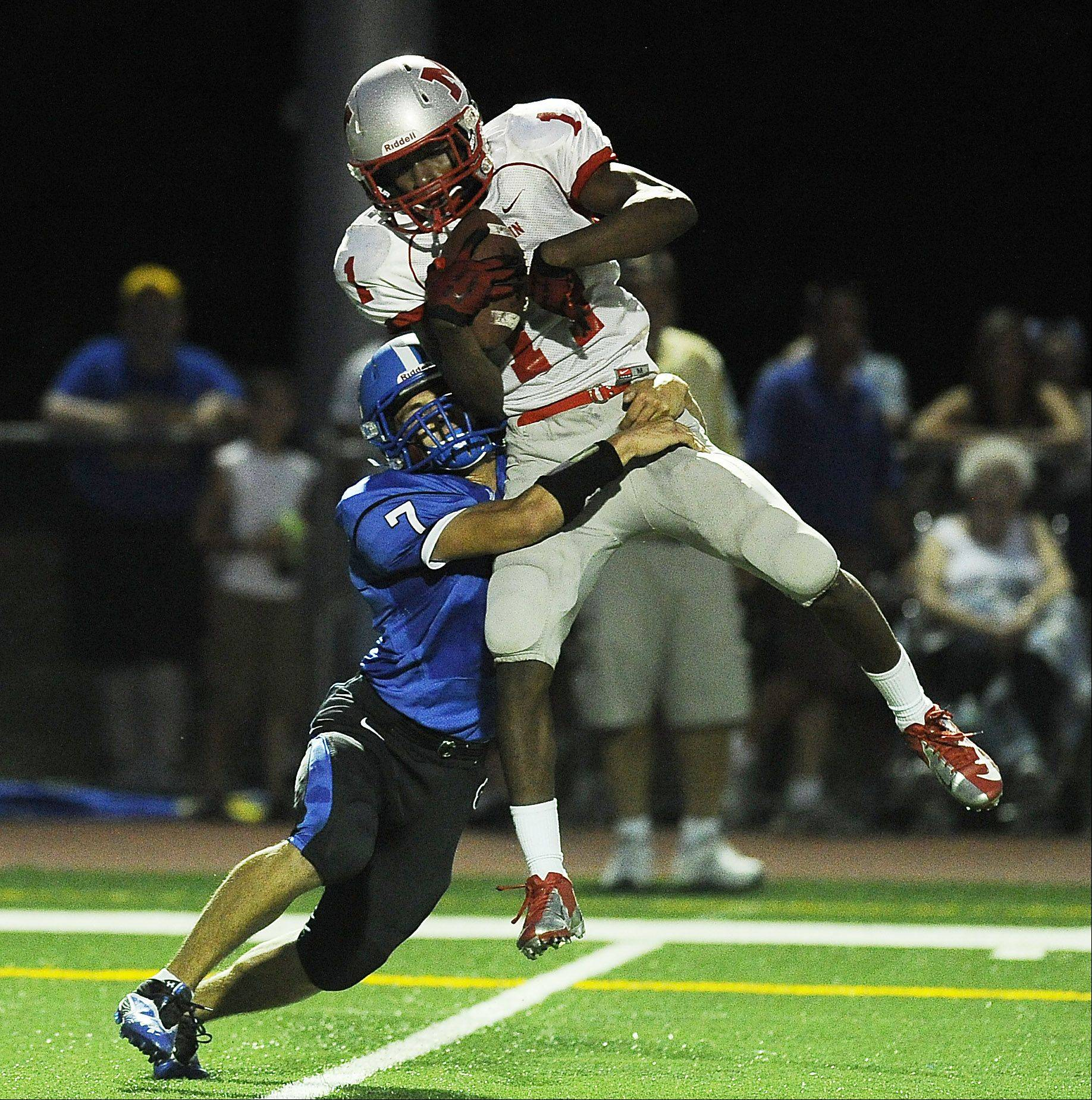 Mundelein's Chance Lindsey hauls in a second-quarter reception under pressure from Wheeling's Michael Yoshino.