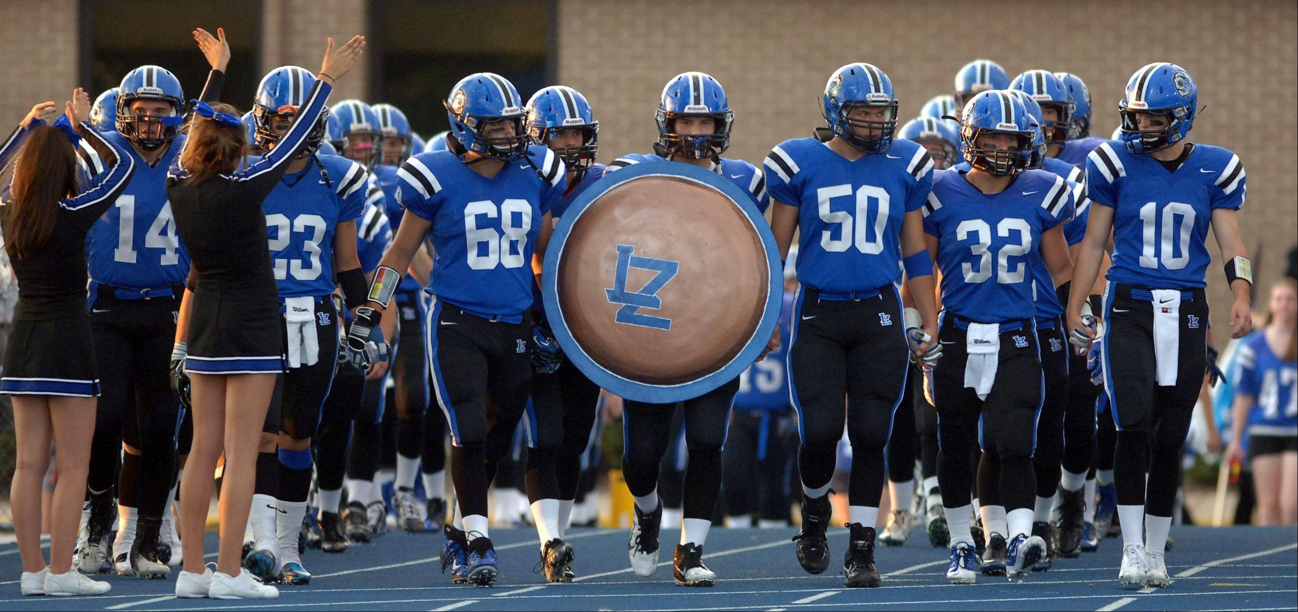 The Lake Zurich Bears head onto the field to face the Fremd Vikings .