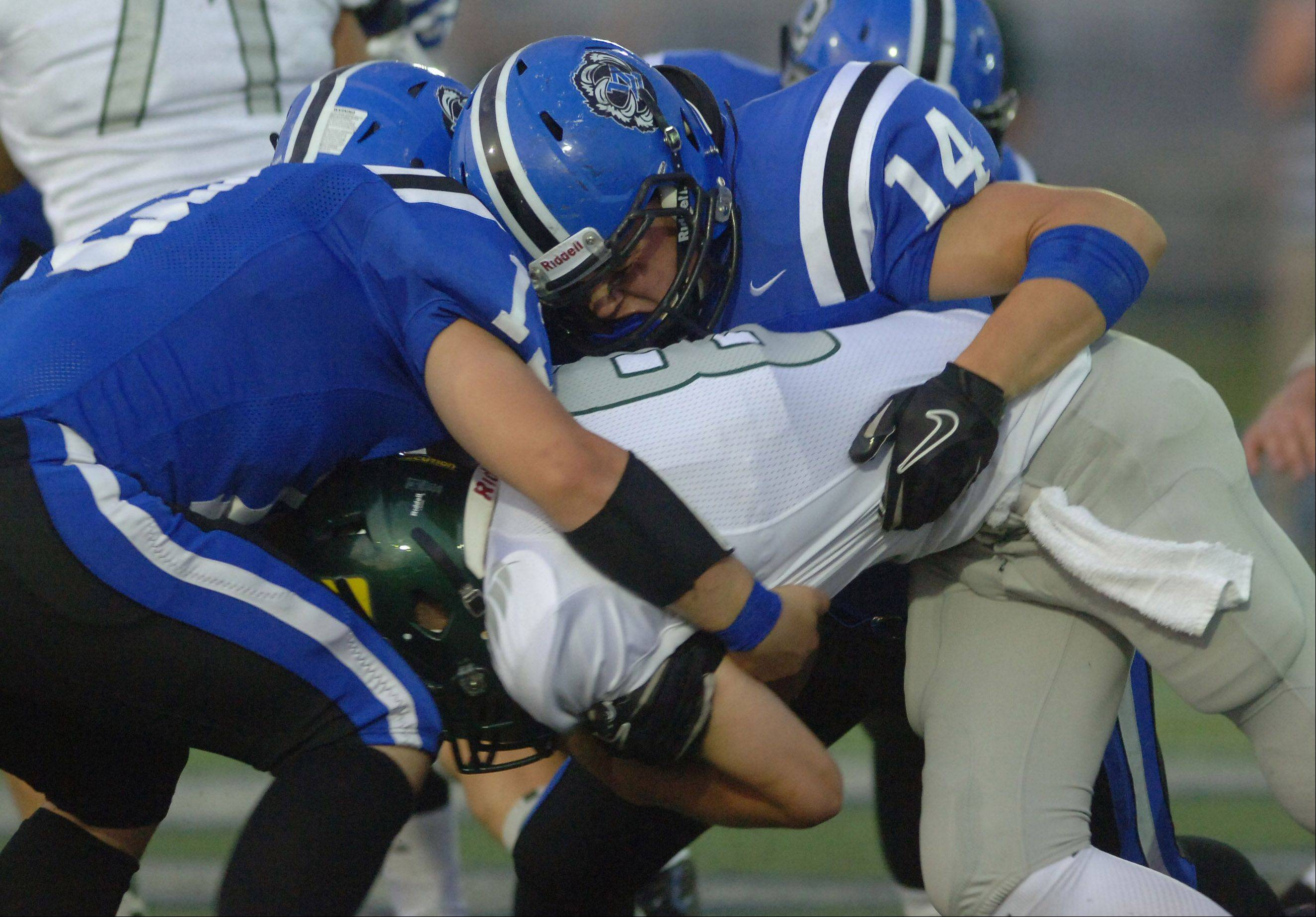 Lake Zurich Bears Christopher Lehtinen, left, and Tanner Kiser wrap up Fremd quarterback Sam Beutler.