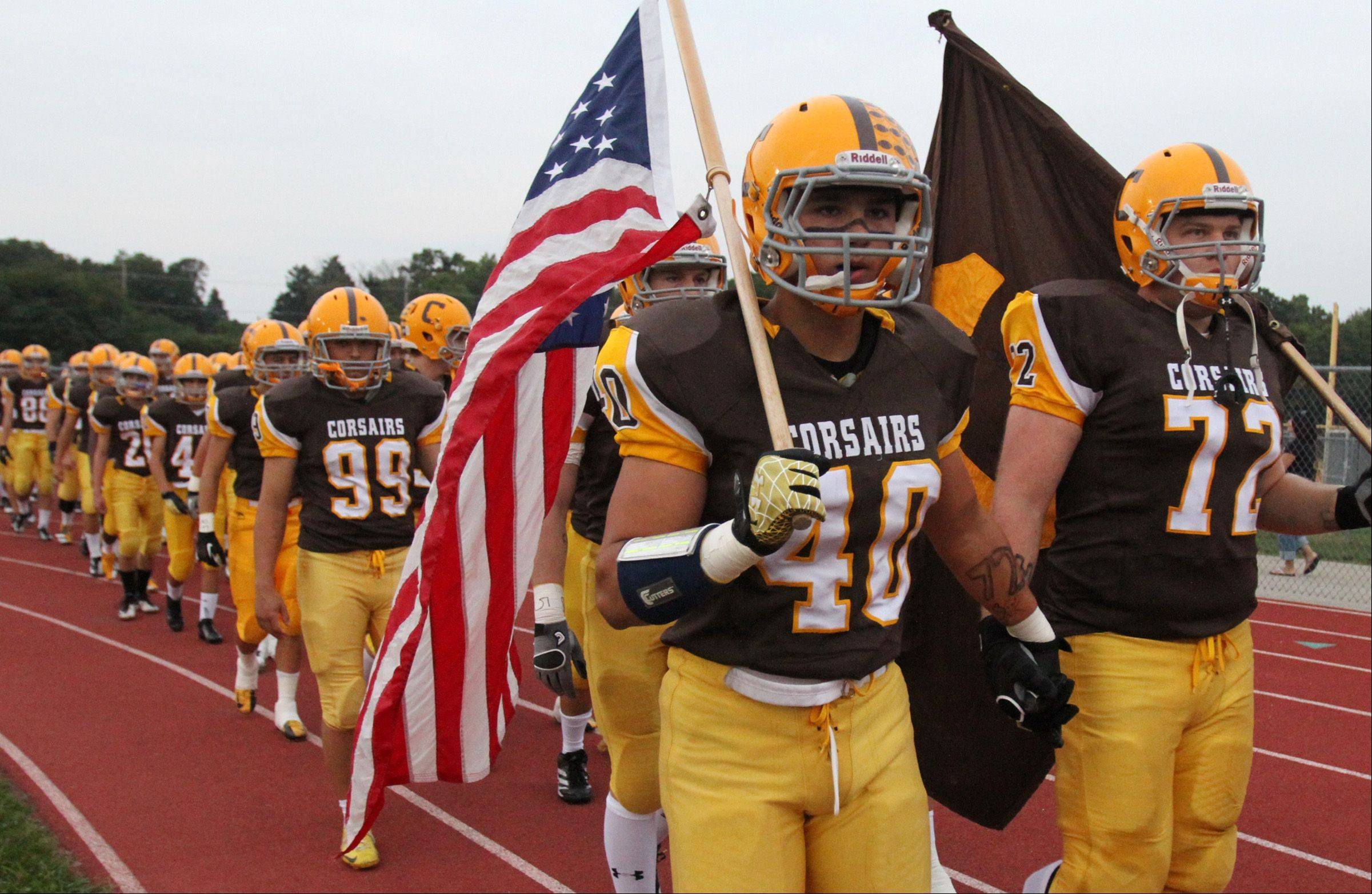 Carmel's Brett Blum cares the American flag and teammate Matt Crisp cares the Carmel High School flag before their game against Glenbard North at Carmel on Friday.