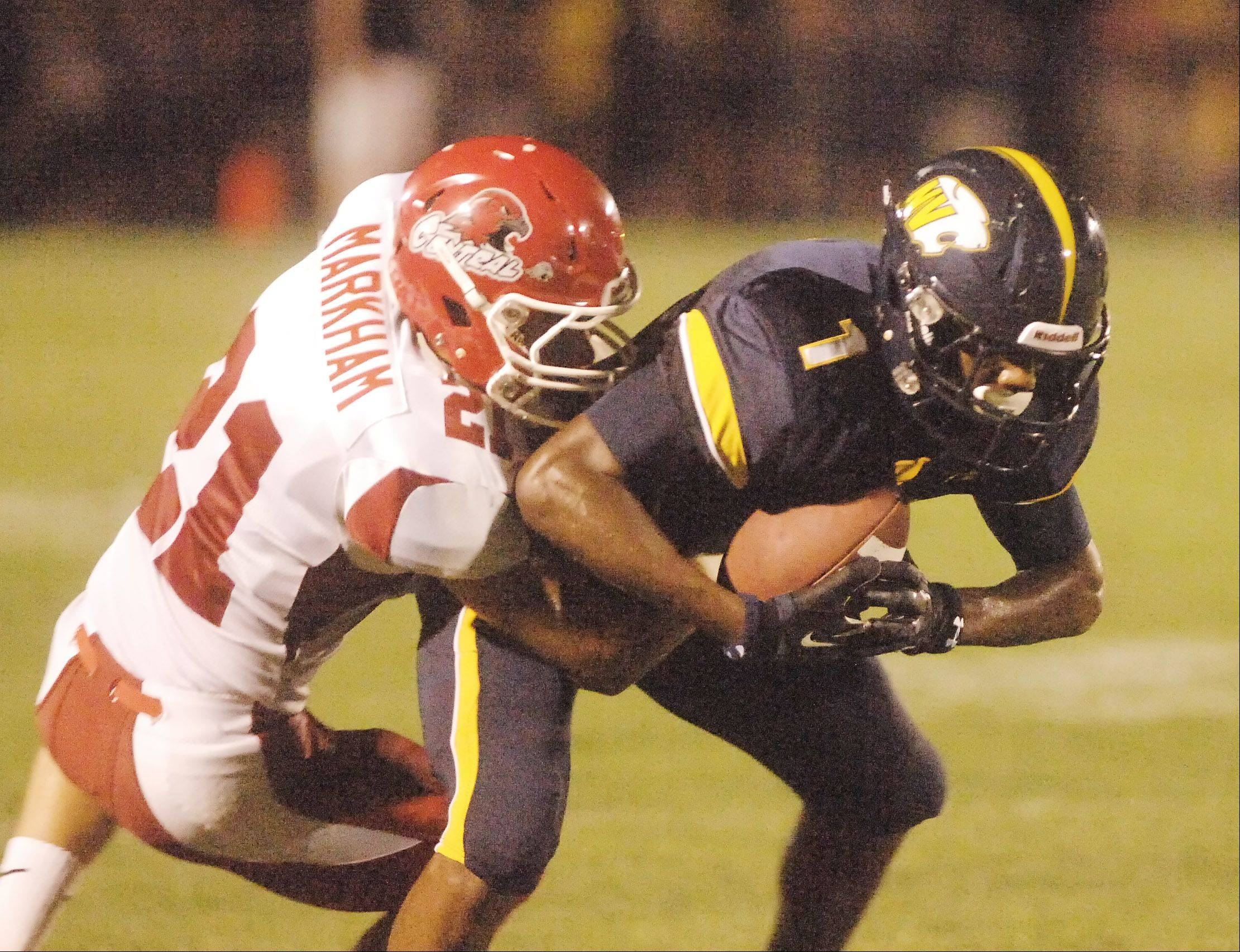 Paul Michna/pmichna@dailyherald.comJustin Markham of Naperville Central pulls down Reggie Ervin of Neuqua Vally during the Naperville Central at Neuqua Valley football game Friday.
