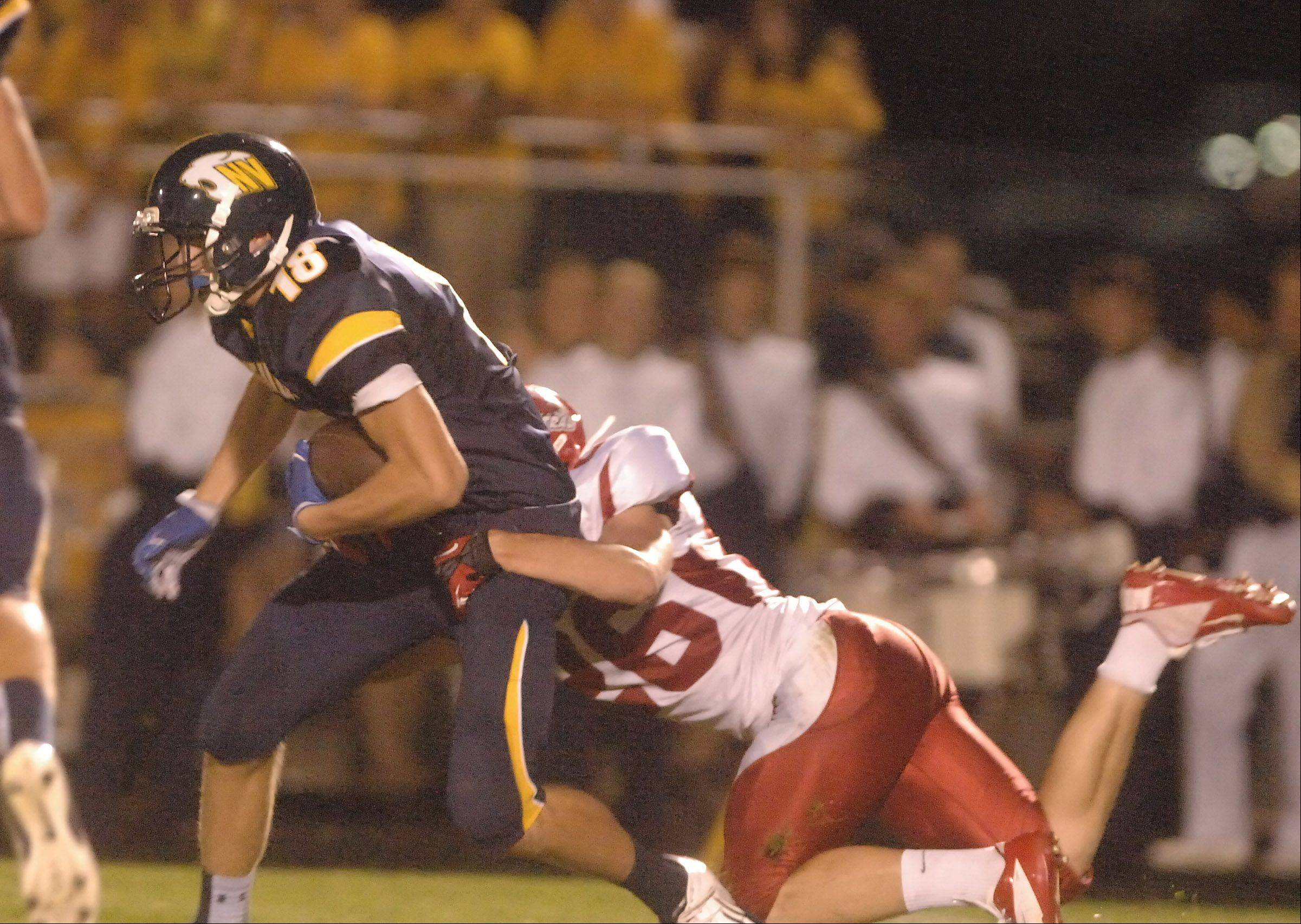 Paul Michna/pmichna@dailyherald.com Ryan Kuhl of Neuqua is pulled down by Kevin Nowak of Naperville Central during the Naperville Central at Neuqua Valley football game Friday.
