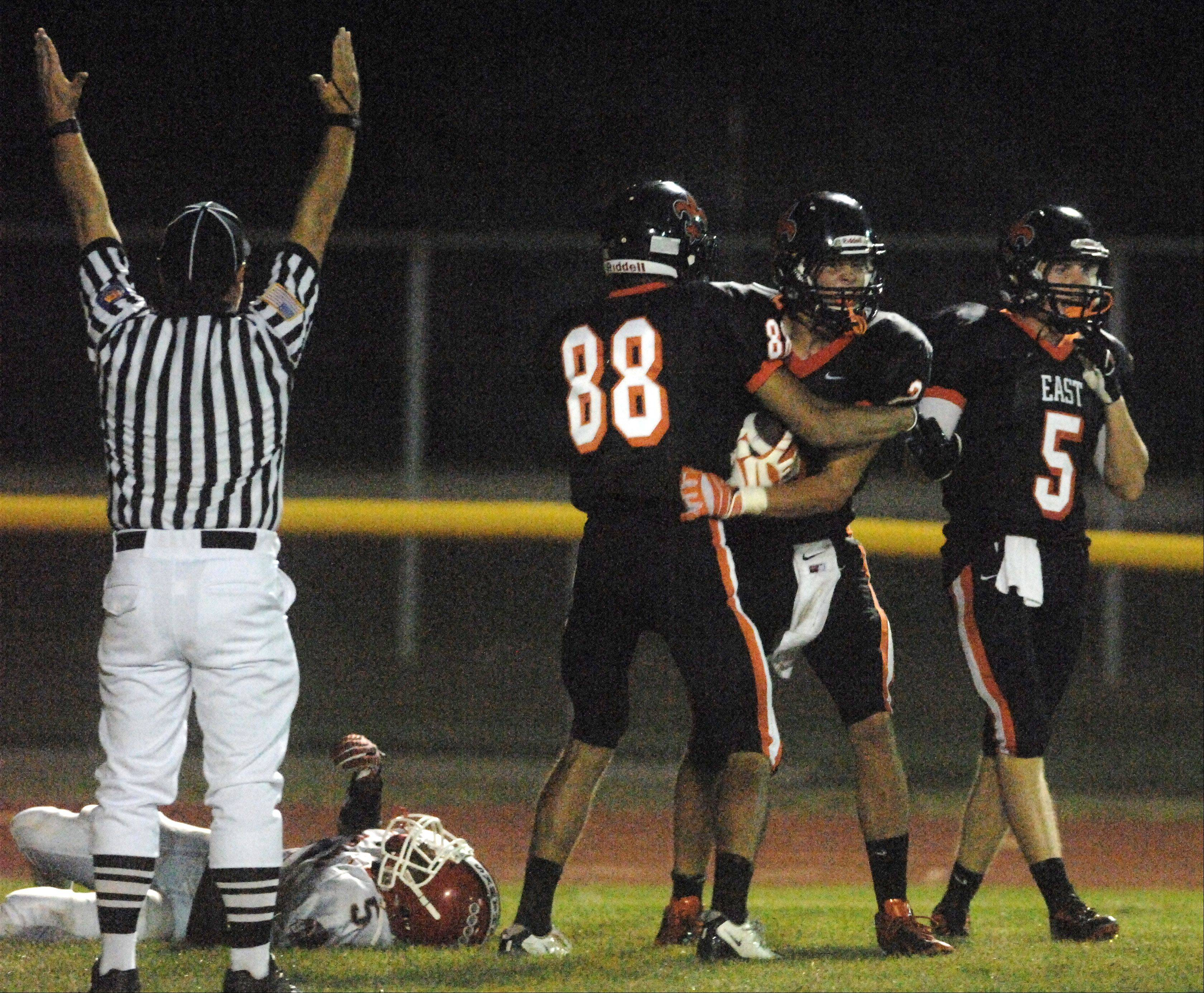 St. Charles East teammates congratulate Barry Brannon, center, after his third quarter touchdown catch against West Aurora during Friday's game in St. Charles.
