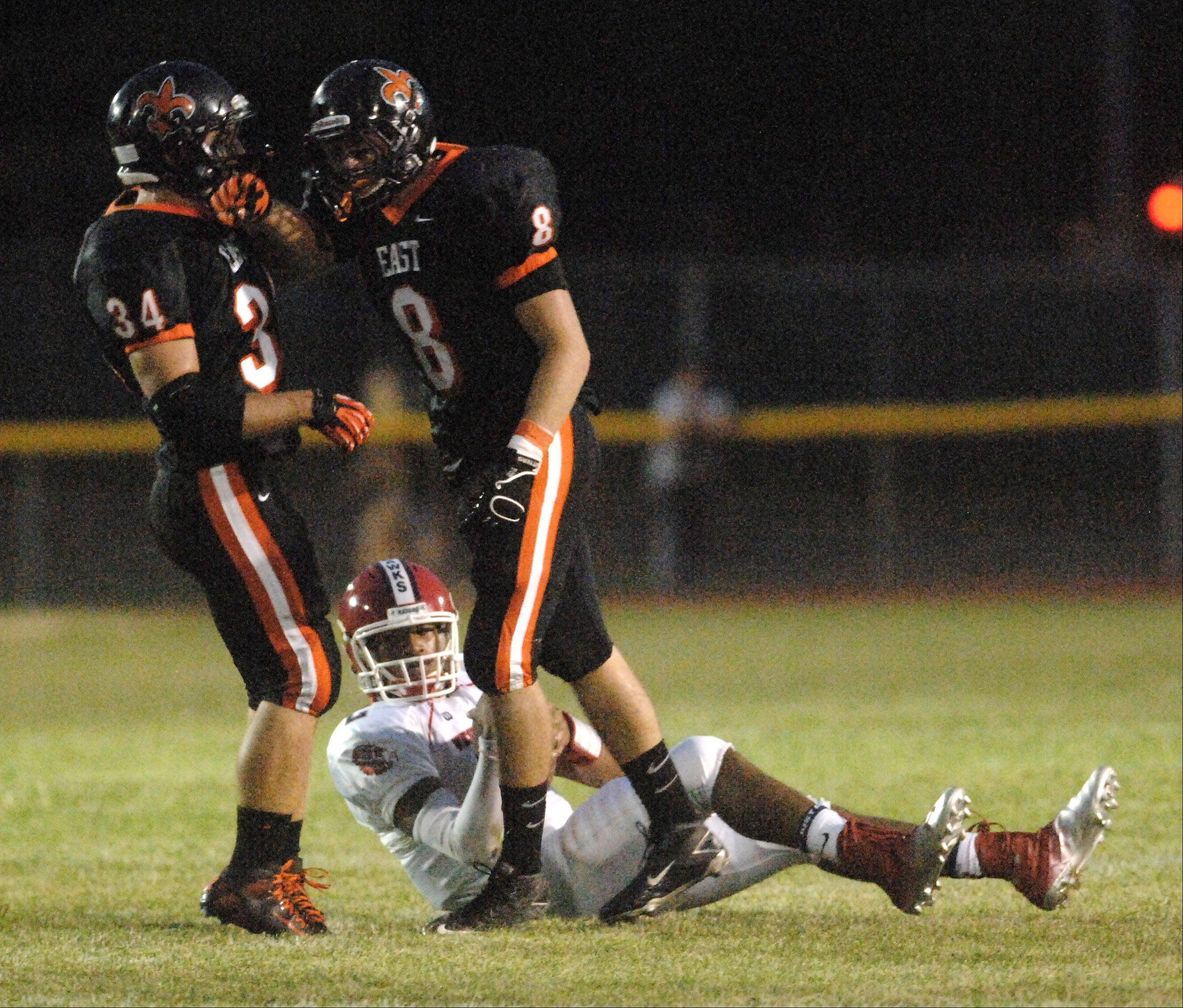 St. Charles East's Joe Hoscheit, left, and Andrew Szyman celebrate a sack of West Aurora quarterback Quintez Jones.