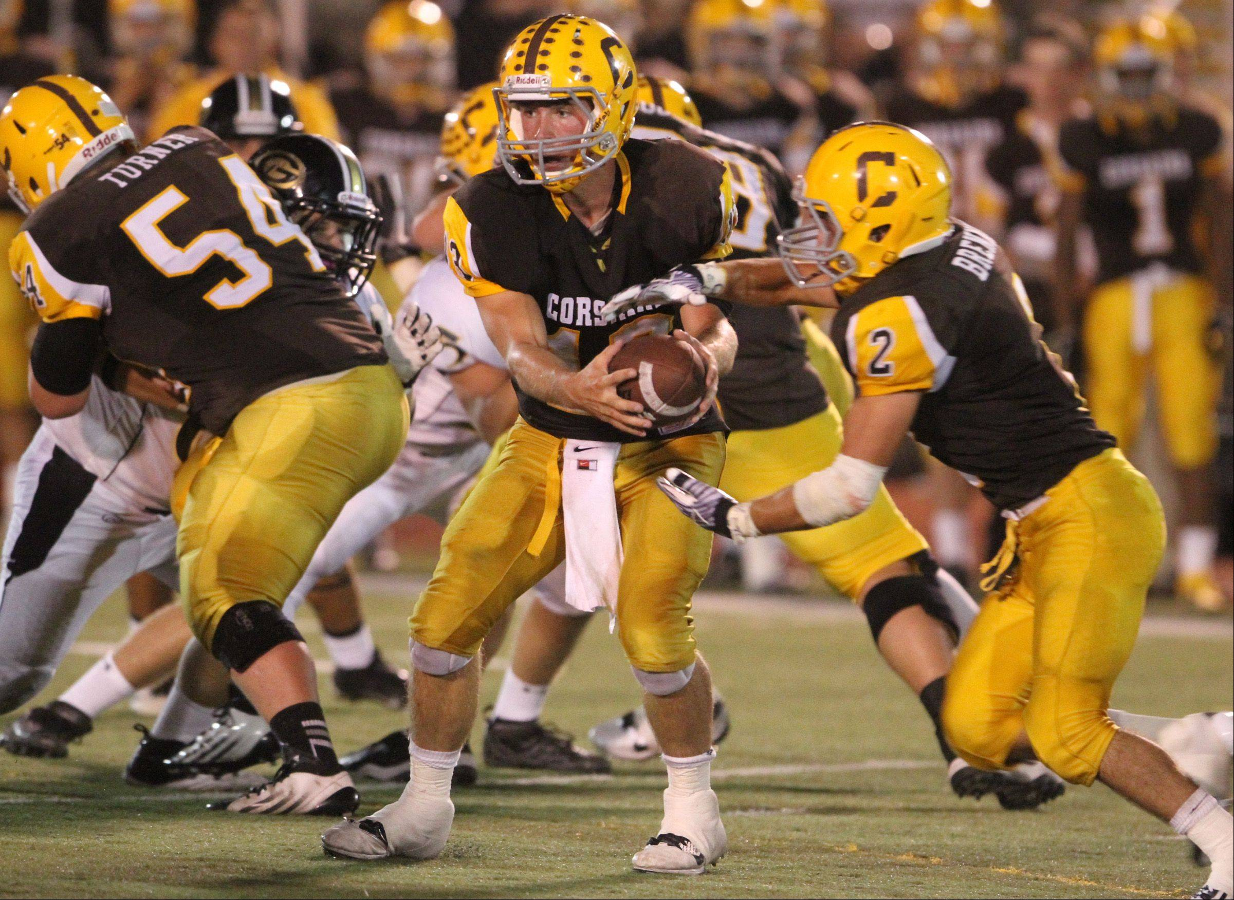 Carmel's quarterback Josh Walinski hands off to running back Sean Brennan.