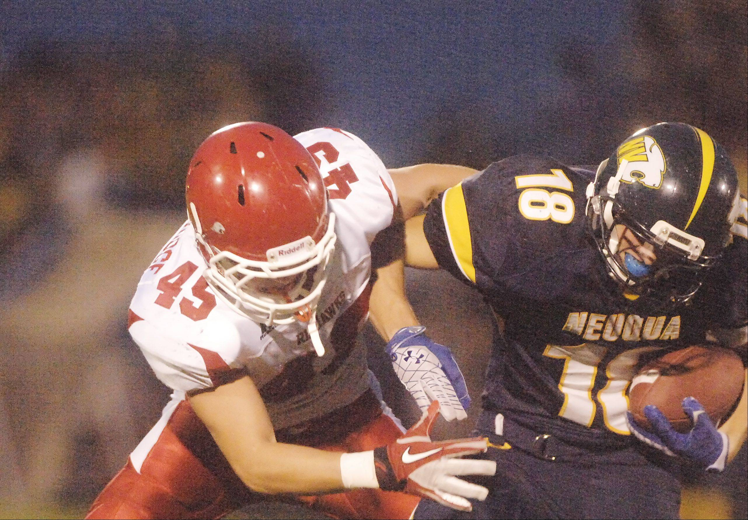 Jack Wooldridge of Naperville Central pulls down Ryan Kuhl of Neuqua Valley.