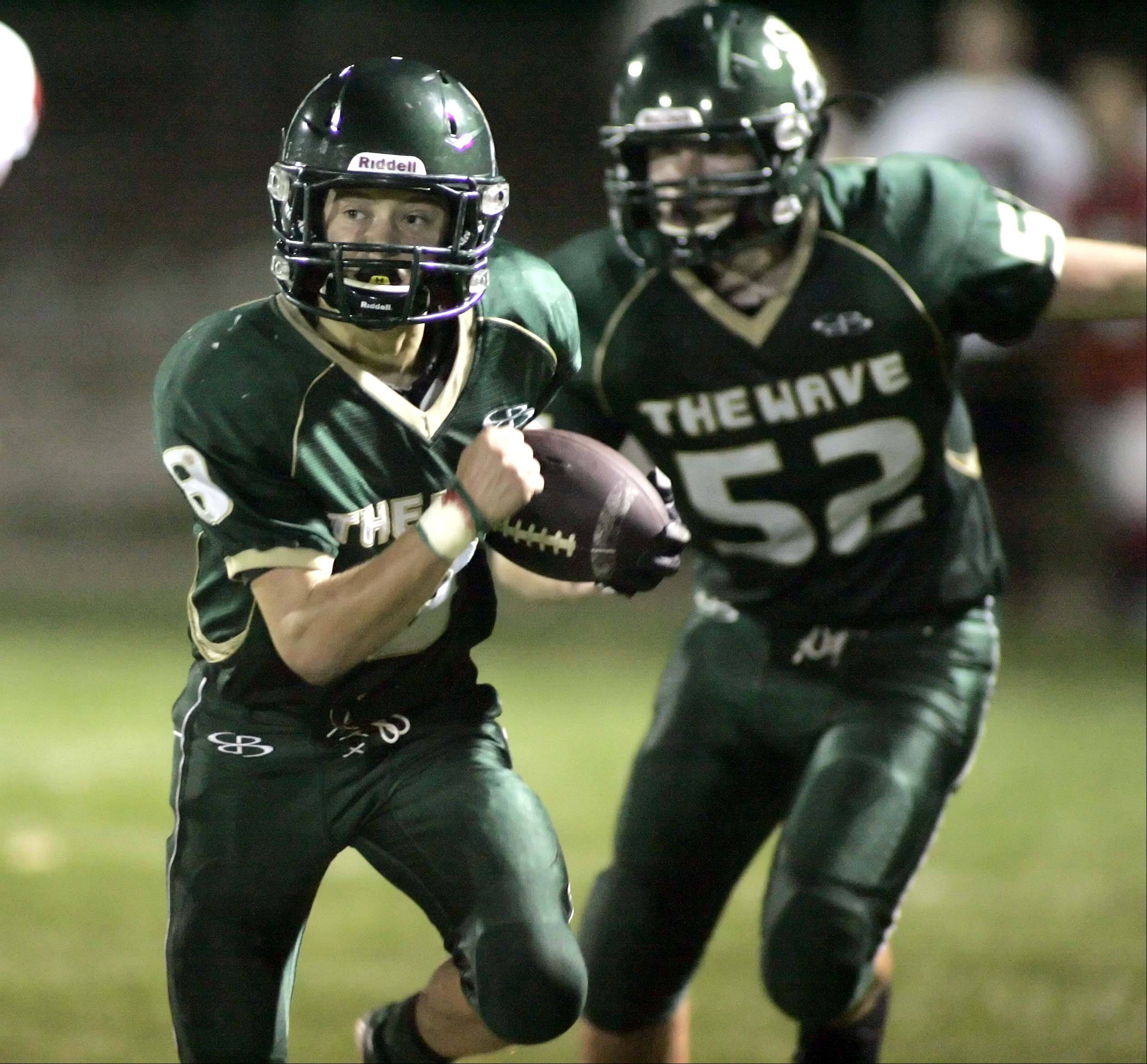 St. Edward's Mikey Castoro moves upfield after pulling in an interception in the second quarter .